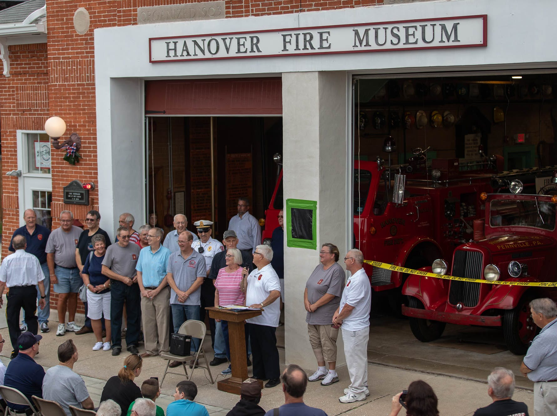 Volunteers and family from the Eagle Fire Company stand together at the podium during the dedication ceremony for the new Greater Hanover Area Fire Museum, Saturday, Sept. 1, 2018, in Hanover.