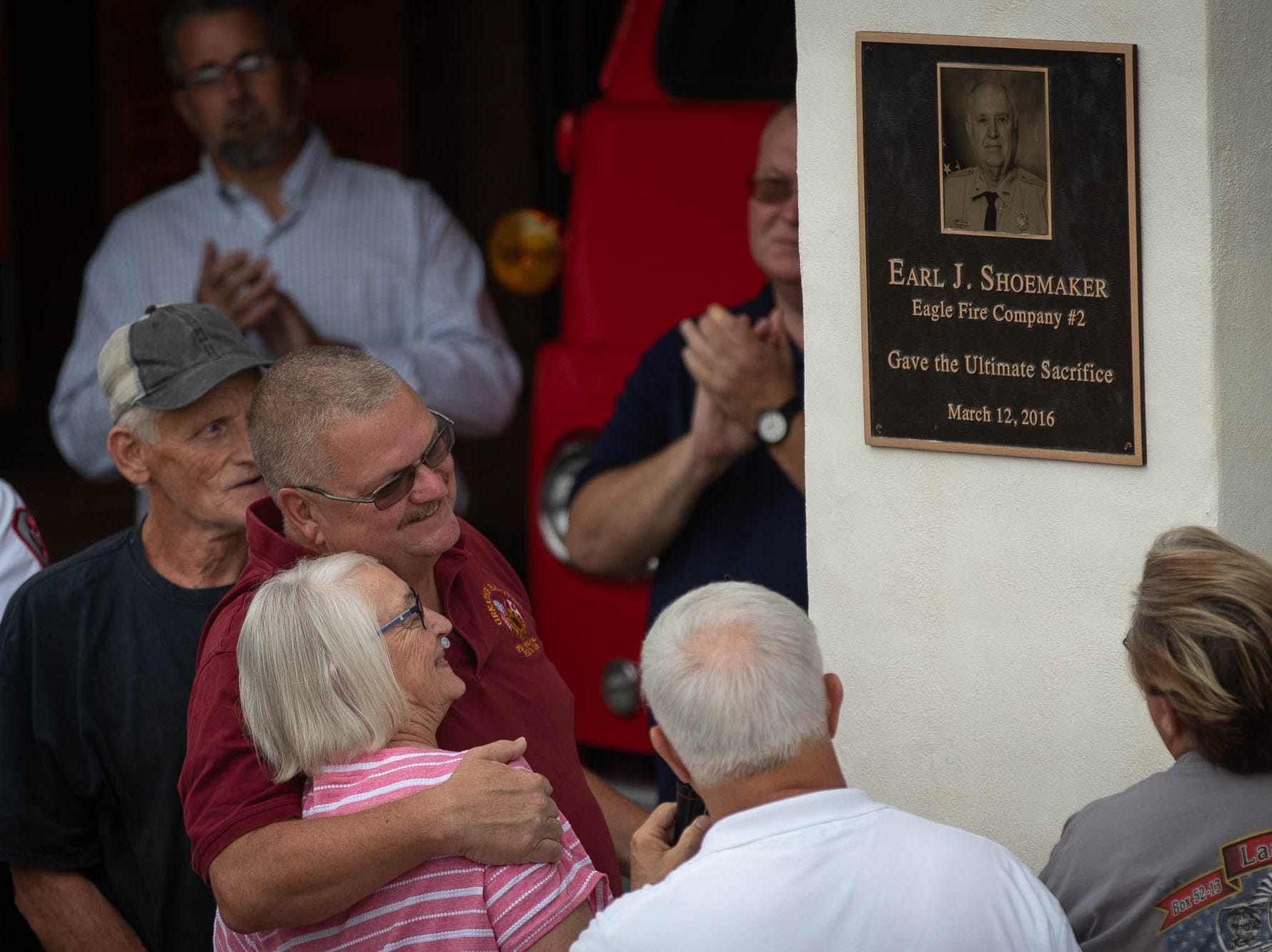 Firefighter Jim Startzel embraces Theresa Shoemaker, wife of fallen firefighter Earl Shoemaker, after they unveiled a plaque in remembrance of Shoemaker during the dedication ceremony for the new Greater Hanover Area Fire Museum, Saturday, Sept. 1, 2018, in Hanover. Earl Shoemaker, a 43-year volunteer of Eagle Fire Company, died in the line of duty while responding to a structure fire March 12, 2016.