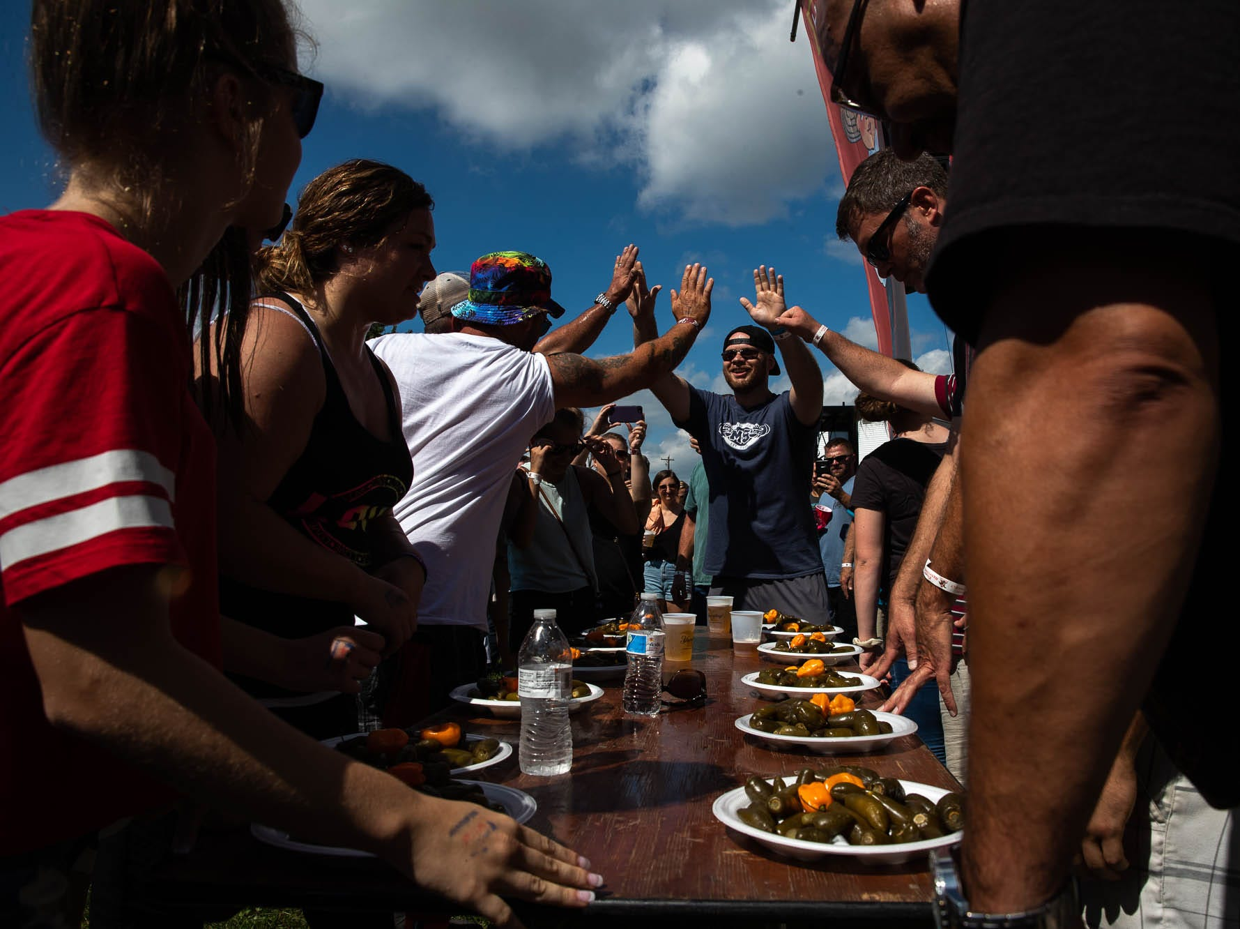 Contestants high-five before a jalapeño pepper-eating contest during the 23rd Annual Hanover Chili Cook Off, Sunday, Sept. 2, 2018, at Good Field in Hanover.