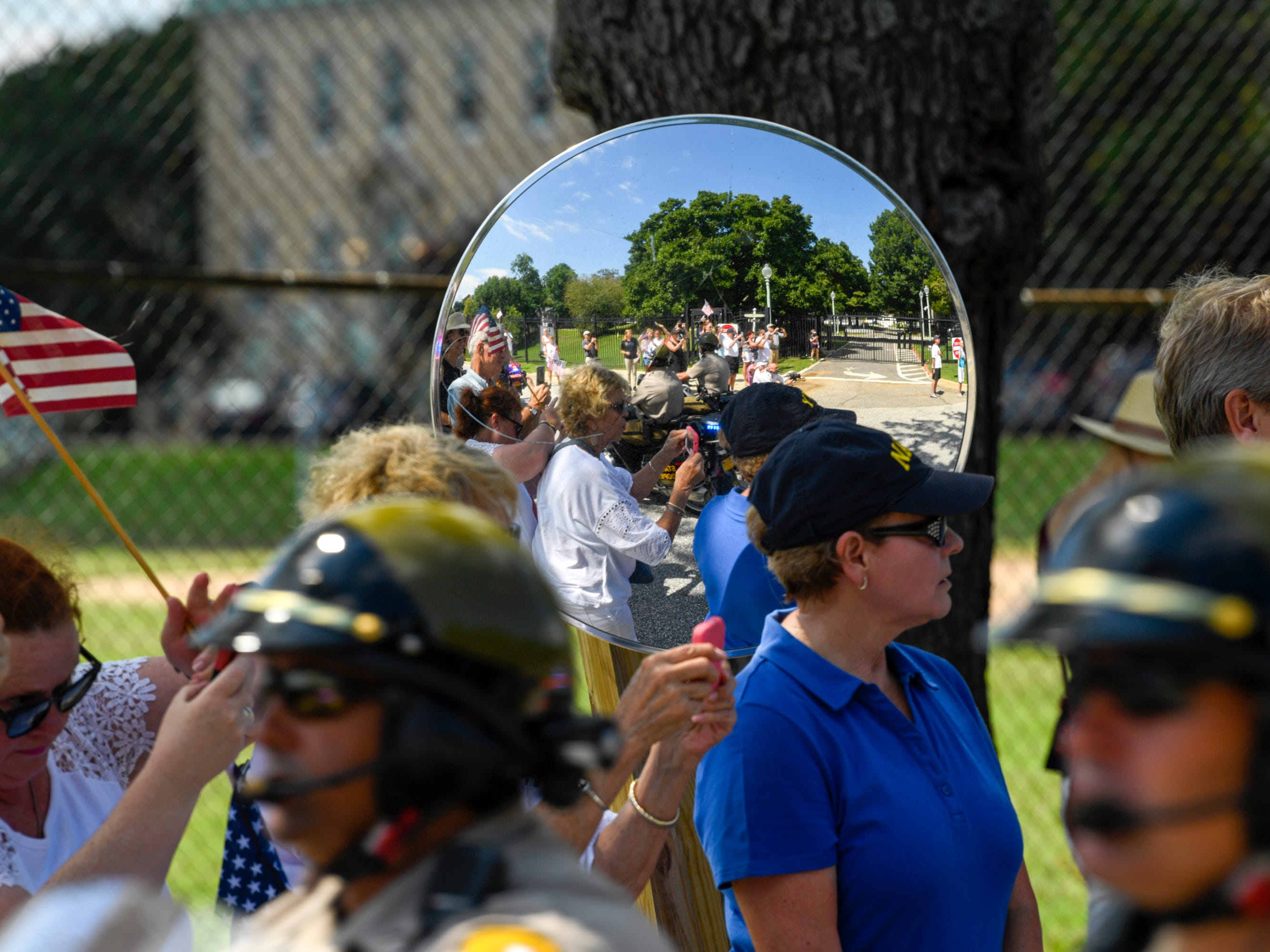 People watch the passing of John McCain's motorcade on his way to be laid to rest at the U.S. Naval Academy in Annapolis, Maryland.