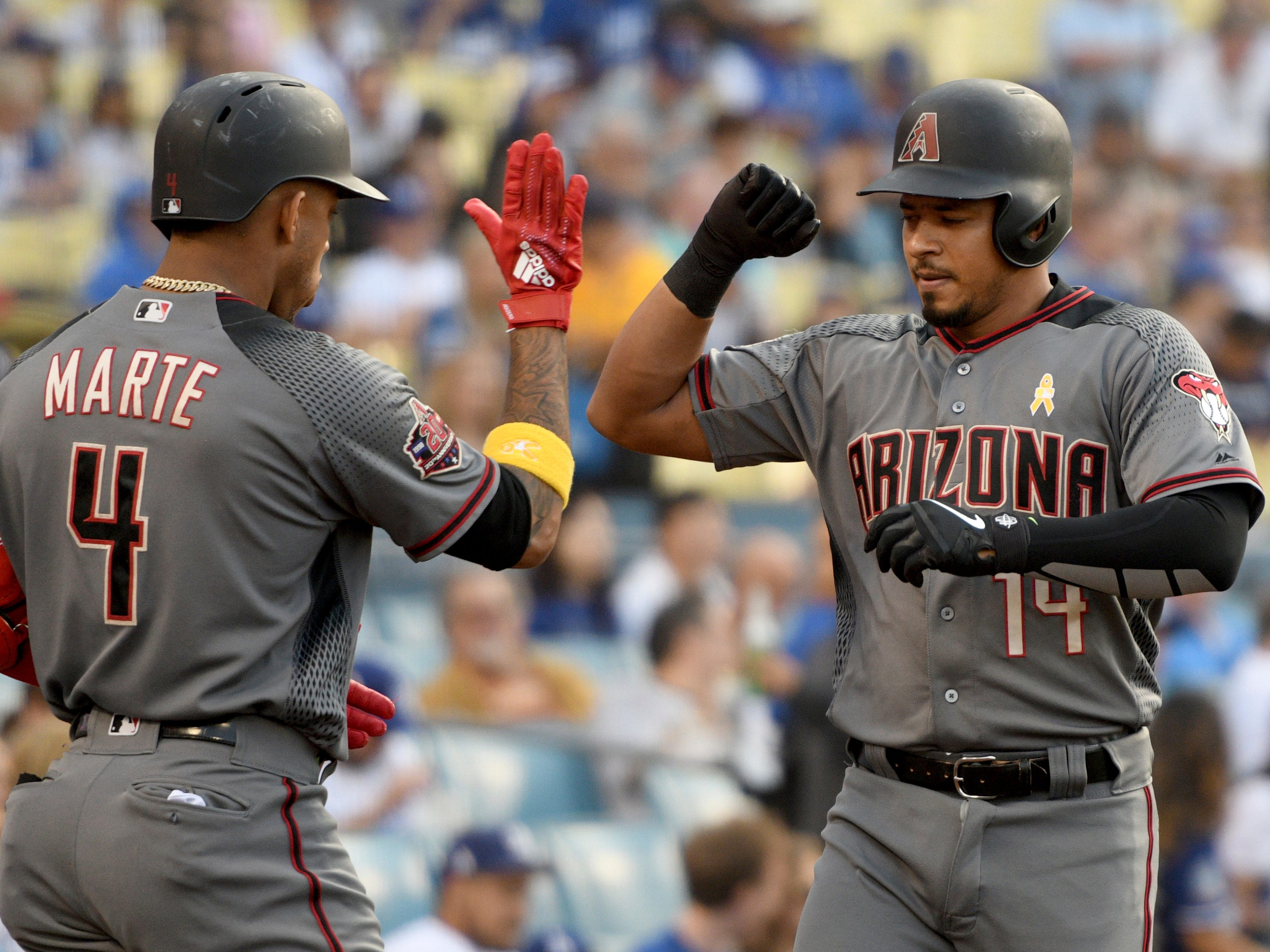 Arizona Diamondbacks' Eduardo Escobar, right, is congratulated by Ketel Marte after Escobar hit a solo home run during the second inning of a baseball game against the Los Angeles Dodgers, Saturday, Sept. 1, 2018, in Los Angeles.