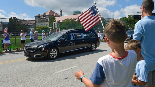 People watch as the casket of Sen. John McCain is brought to Annapolis, Maryland, Sept. 2, 2018, for his funeral service and burial at the U.S. Naval Academy. McCain died Aug. 25 from brain cancer at age 81.