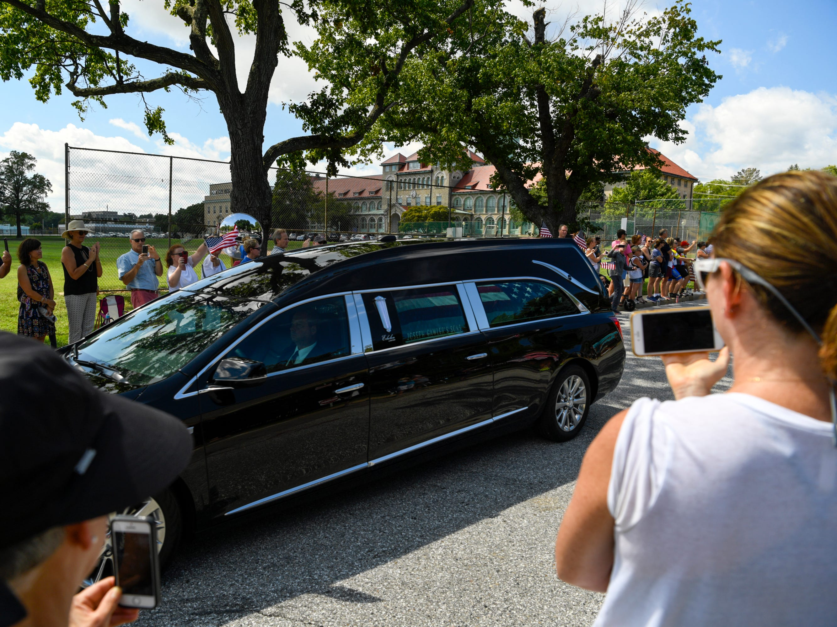 People gather to watch the passing of John McCain's motorcade on his way to be laid to rest at the U.S. Naval Academy in Annapolis, Maryland