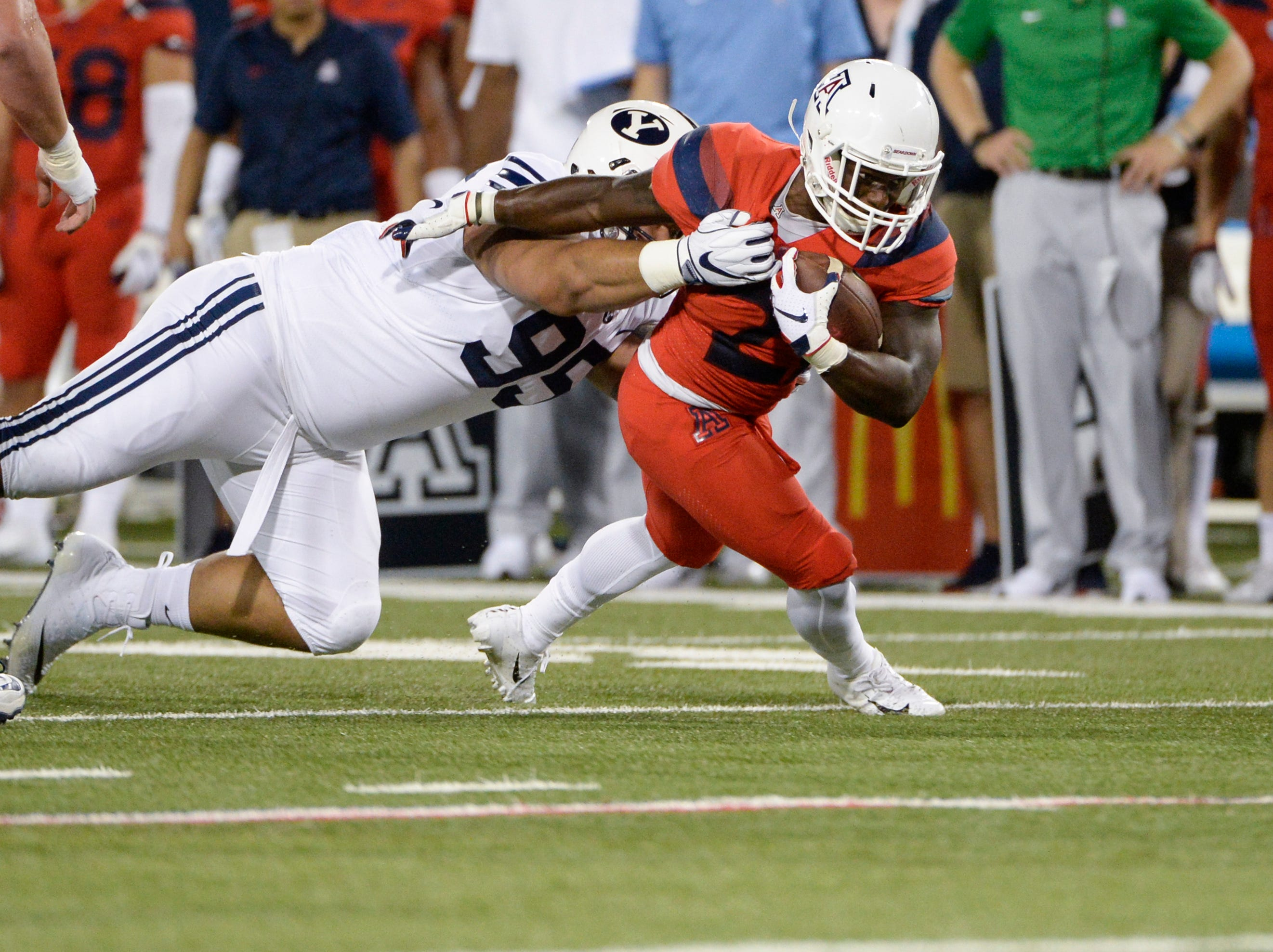 Sep 1, 2018; Tucson, AZ, USA; Arizona Wildcats running back J.J. Taylor (21) runs with the football tackled by Brigham Young Cougars defensive lineman Khyiris Tonga (95) during the first quarter at Arizona Stadium.