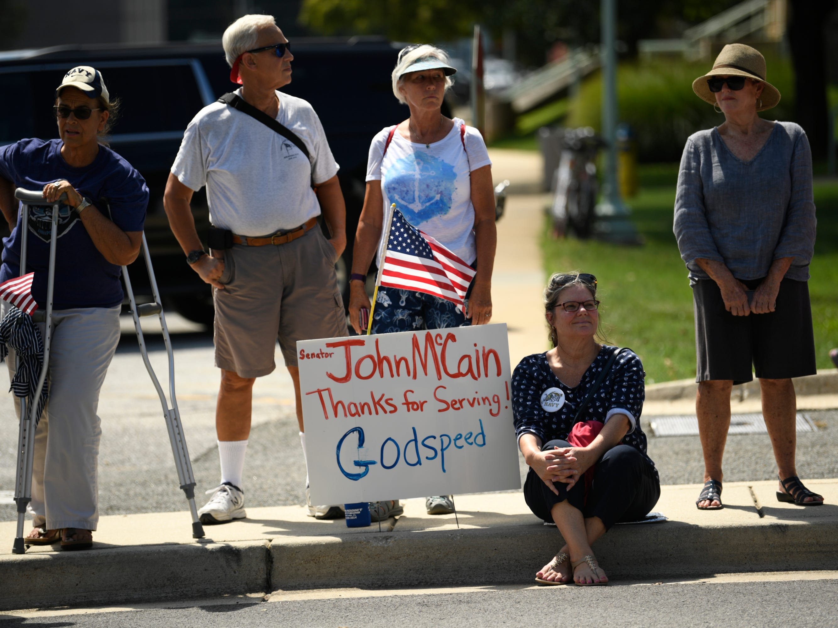 People gather to watch the passing of John McCain's motorcade on his way to be laid to rest at the U.S. Naval Academy in Annapolis, Maryland.