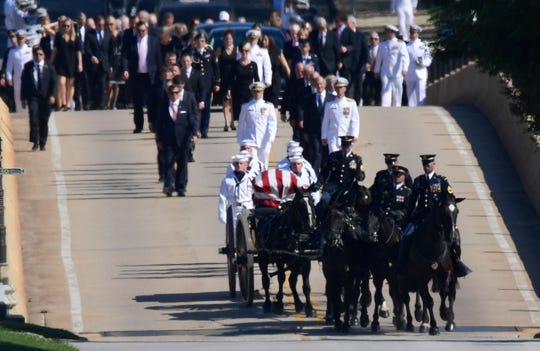 Family members, including Cindy McCain (back center) follow a horse-drawn caisson that carries the casket of Sen. John McCain as it proceeds to the United States Naval Academy cemetery in Annapolis, Maryland, Sept. 2, 2018, for burial. McCain died Aug. 25 from brain cancer at age 81