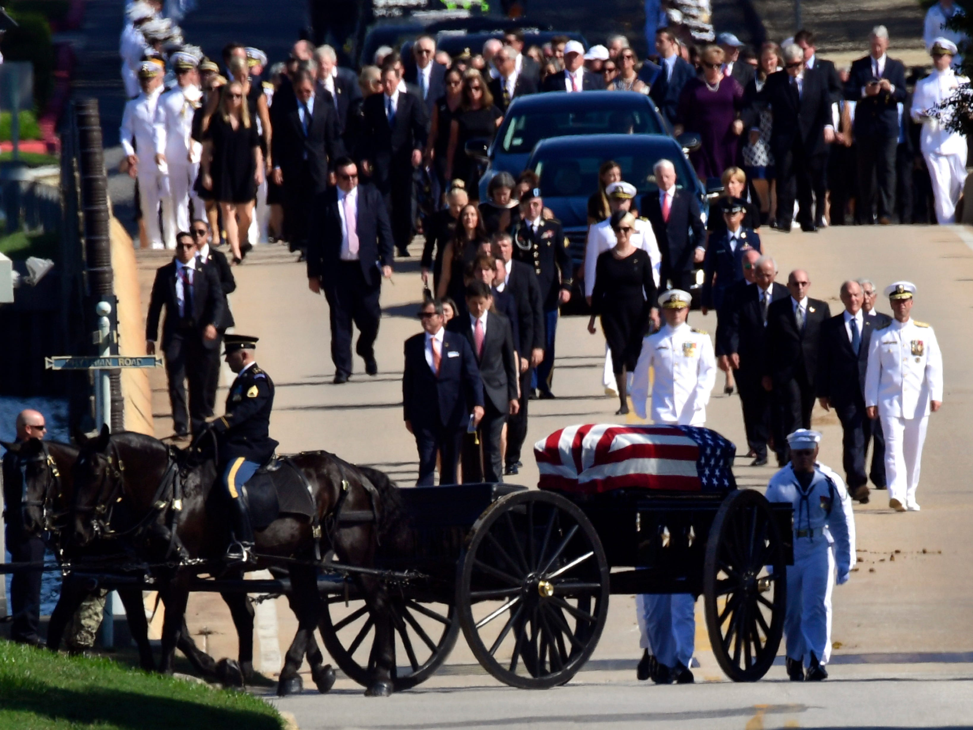 Family members, including Cindy McCain (back center) follow a horse-drawn caisson that carries the casket of Sen. John McCain as it proceeds to the United States Naval Academy cemetery in Annapolis, Maryland, Sept. 2, 2018, for burial. McCain died Aug. 25 from brain cancer at age 81.