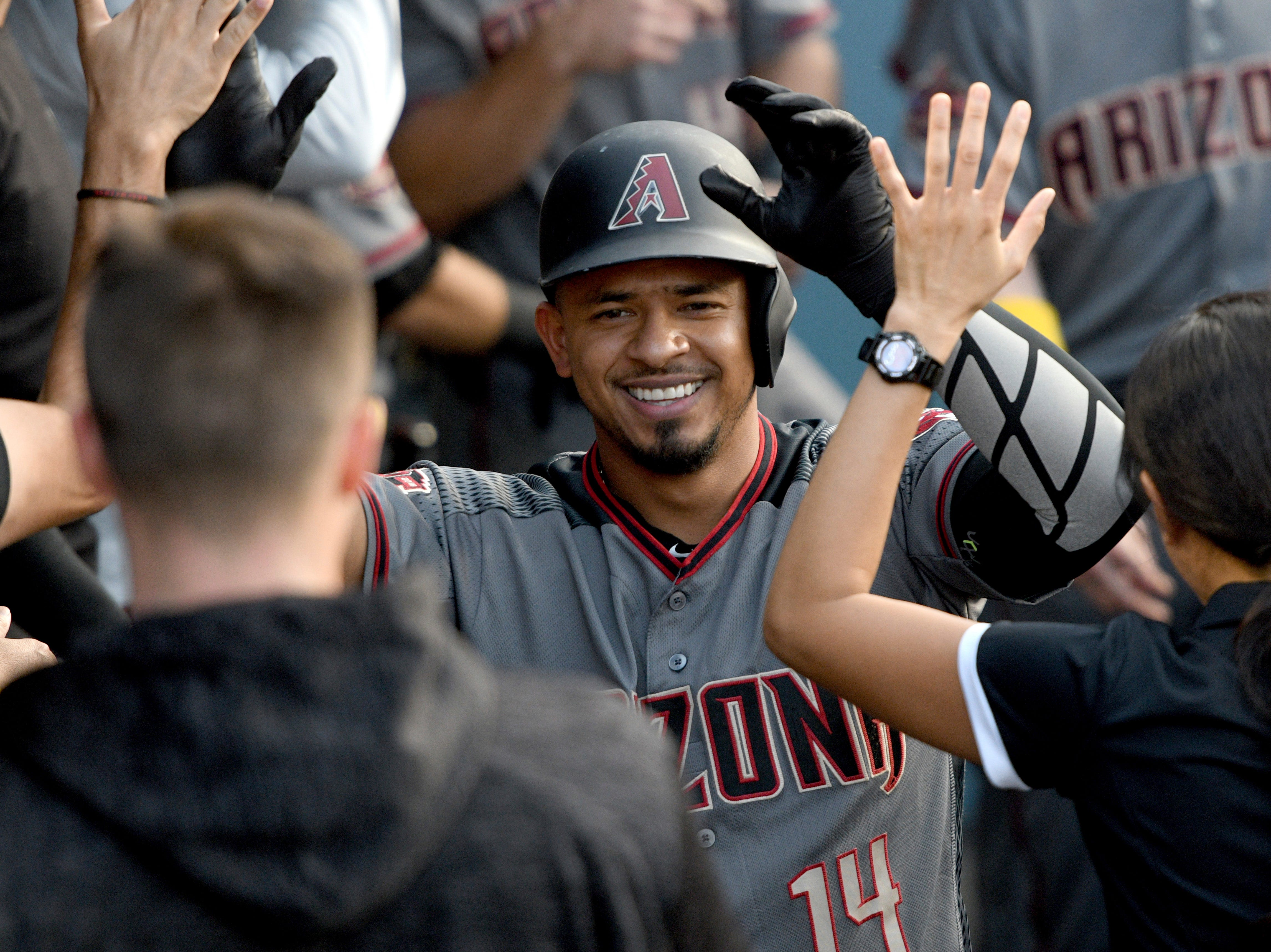 Arizona Diamondbacks' Eduardo Escobar (14) is congratulated in the dugout after hitting a solo home run during the second inning of a baseball game against the Los Angeles Dodgers, Saturday, Sept. 1, 2018, in Los Angeles.
