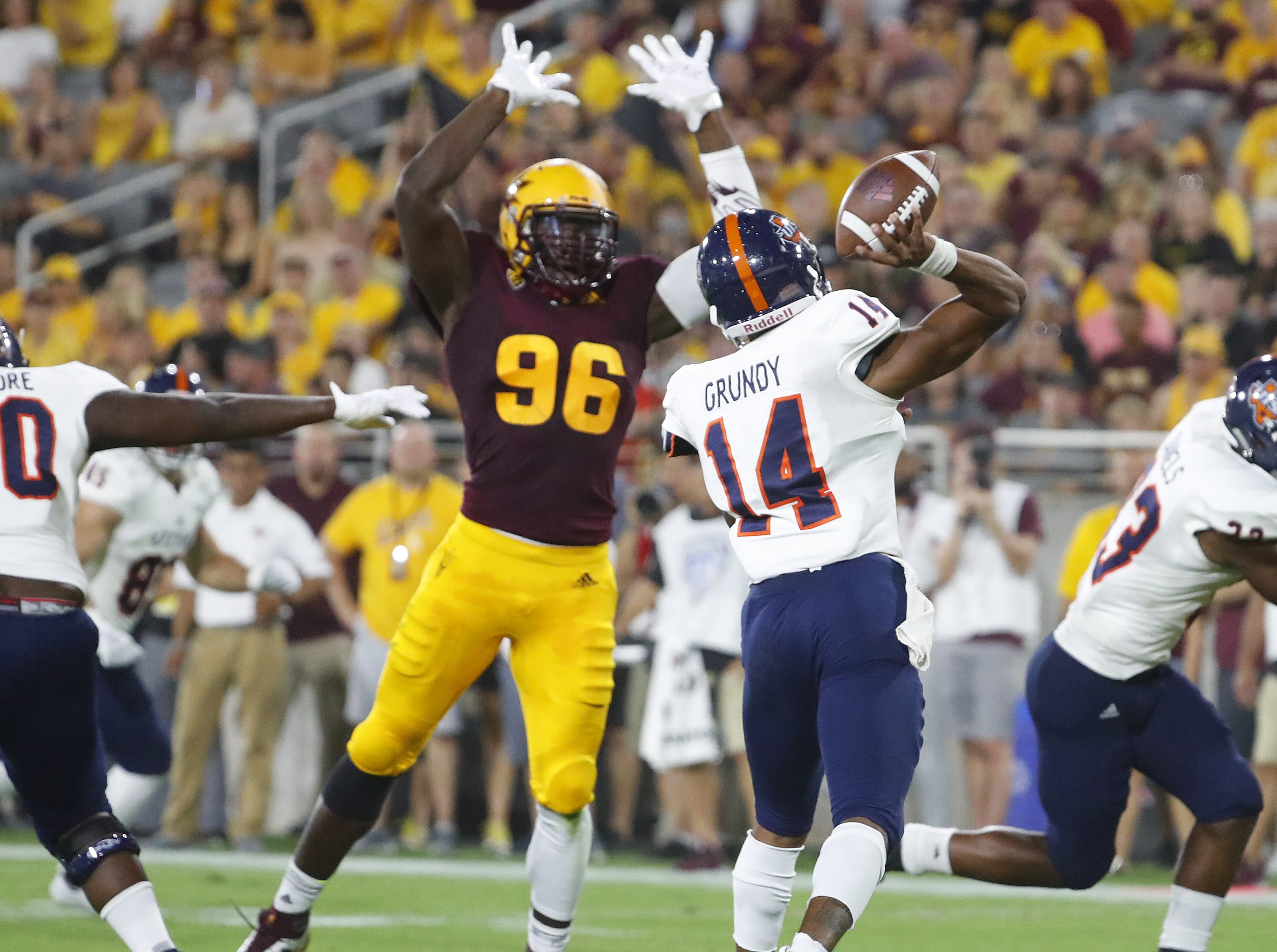 UTSA Roadrunners quarterback Cordale Grundy (14) throws a pass under pressure from Arizona State Sun Devils defensive lineman Jalen Bates (96) during the first half at Sun Devil Stadium in Tempe, Ariz. on Sept. 1, 2018.
