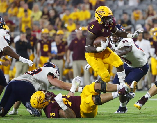 Arizona State Sun Devils running back Eno Benjamin (3) leaps over teammate Arizona State Sun Devils offensive lineman Cohl Cabral (73) against UTSA during the second half at Sun Devil Stadium in Tempe, Ariz. on Sept. 1, 2018.