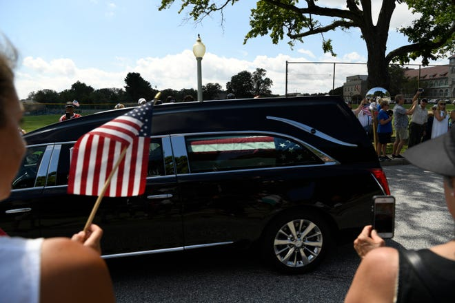 Bella Petrides (left) watches and waves her flag at the passing of John McCain's motorcade on his way to be laid to rest at the U.S. Naval Academy in Annapolis, Maryland.