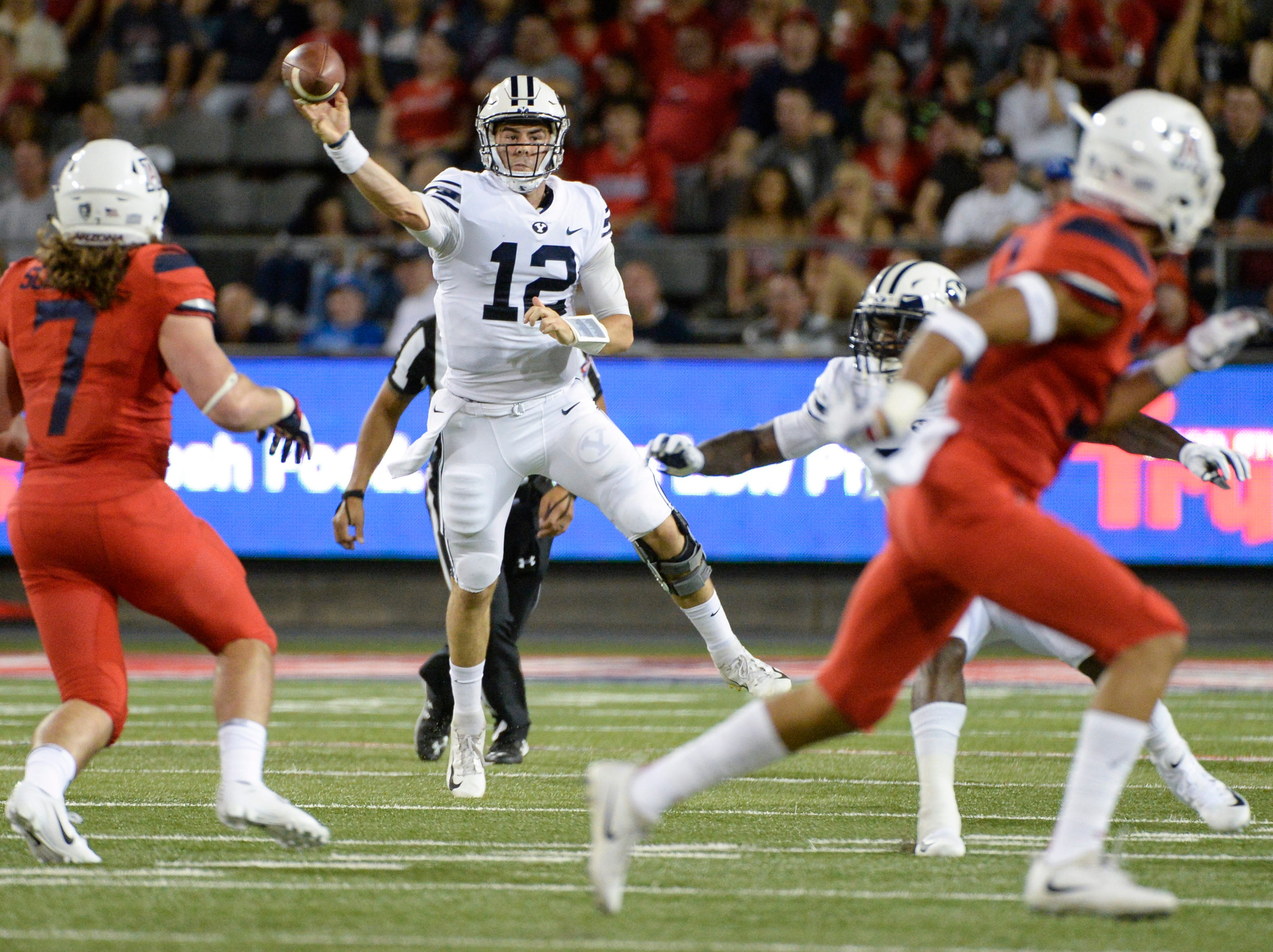 Sep 1, 2018; Tucson, AZ, USA; Brigham Young Cougars quarterback Tanner Mangum (12) passes the ball under pressure from Arizona Wildcats linebacker Colin Schooler (7) during the first quarter at Arizona Stadium.