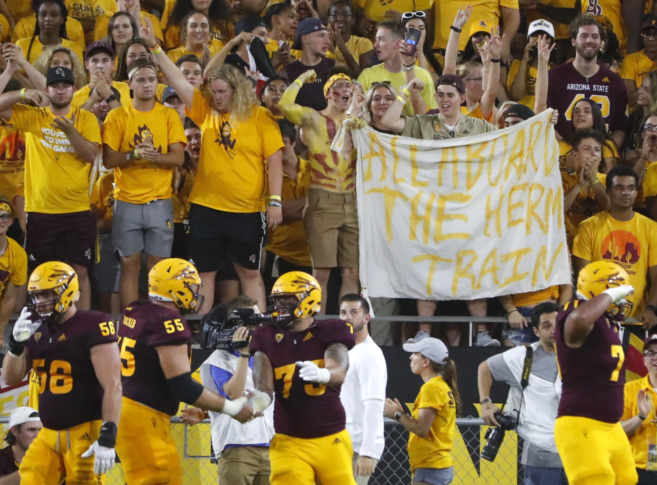 "ASU fans hold up a ""All aboard the Herm Train"" sign after Arizona State Sun Devils wide receiver Terrell Chatman (19) catches a touchdown pass during the second quarter against UTSA at Sun Devil Stadium in Tempe, Ariz. on Sept. 1, 2018."