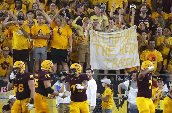 """ASU fans hold up a """"All aboard the Herm Train"""" sign after Arizona State Sun Devils wide receiver Terrell Chatman (19) catches a touchdown pass during the second quarter against UTSA at Sun Devil Stadium in Tempe, Ariz. on Sept. 1, 2018."""