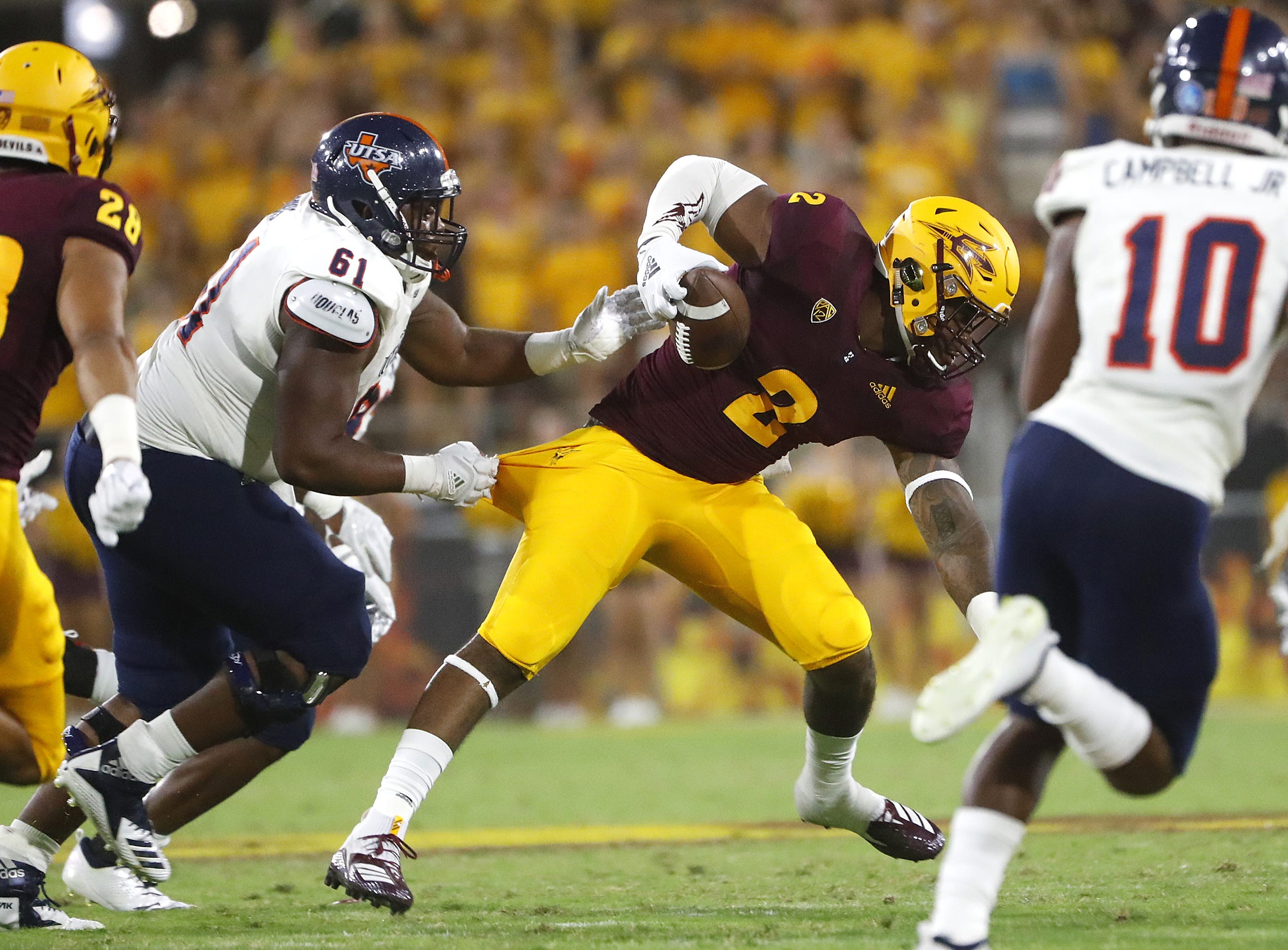 UTSA Roadrunners offensive lineman Kevin Davis (61) tackles Arizona State Sun Devils defensive lineman Darius Slade (2) after Slade picked up a fumble during the first half at Sun Devil Stadium in Tempe, Ariz. on Sept. 1, 2018.