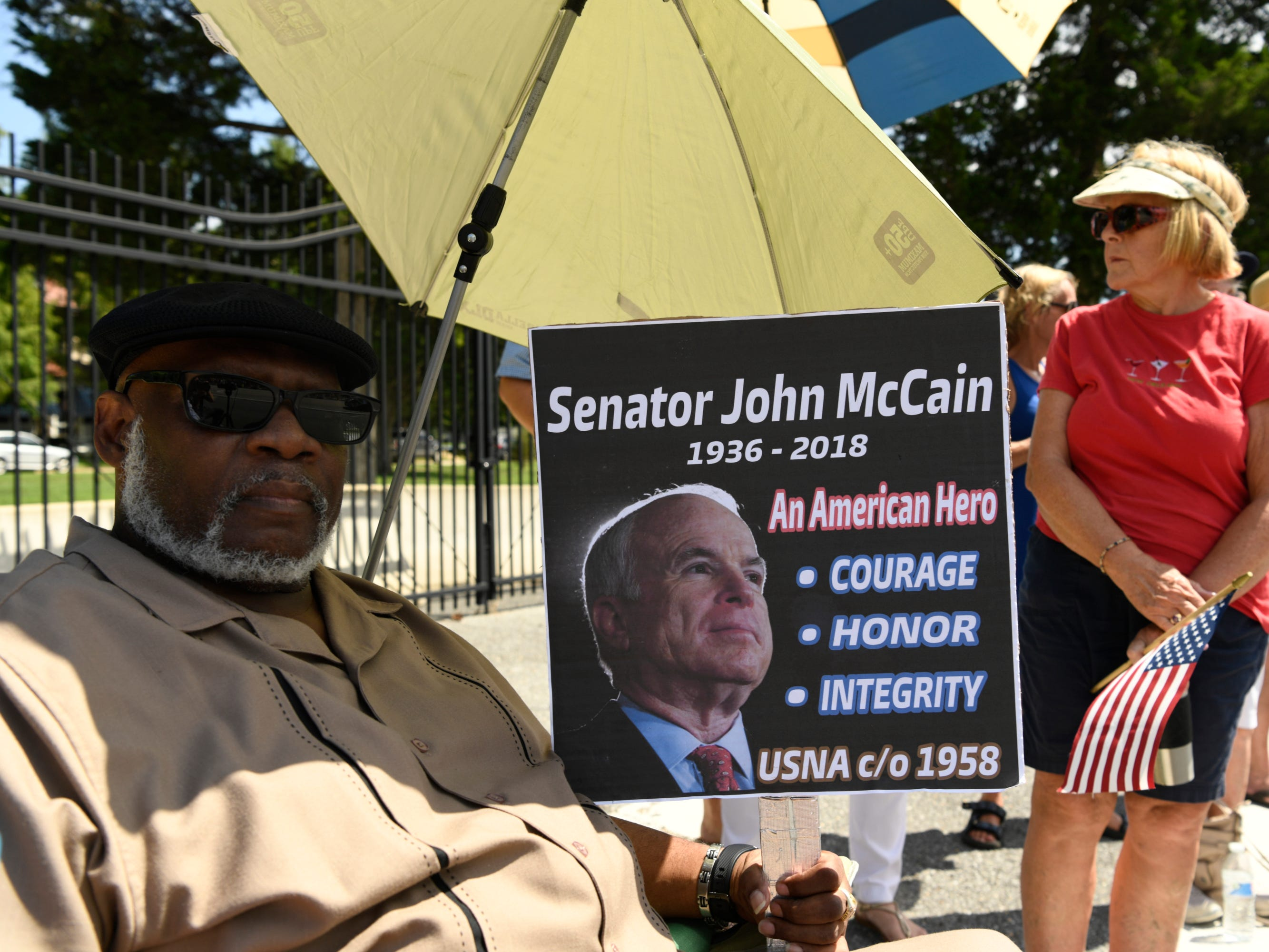 Charles James Sr. sits with a sign he made to watch the passing of John McCain's motorcade on his way to be laid to rest at the U.S. Naval Academy in Annapolis, Maryland.