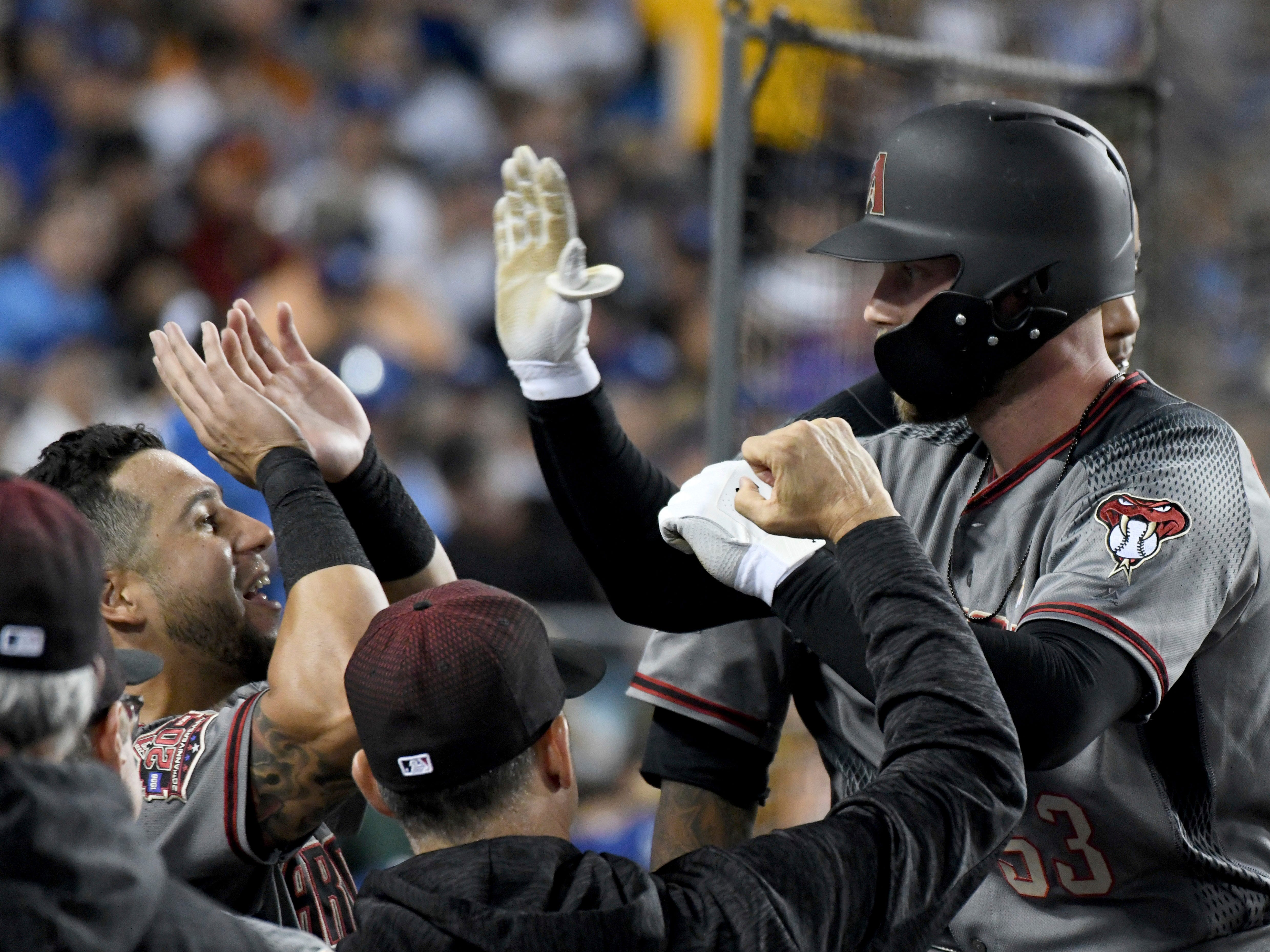 Arizona Diamondbacks' Christian Walker (53) is congratulated in the dugout after hitting a solo home run in the sixth inning of a baseball game against the Los Angeles Dodgers, Saturday, Sept. 1, 2018, in Los Angeles.