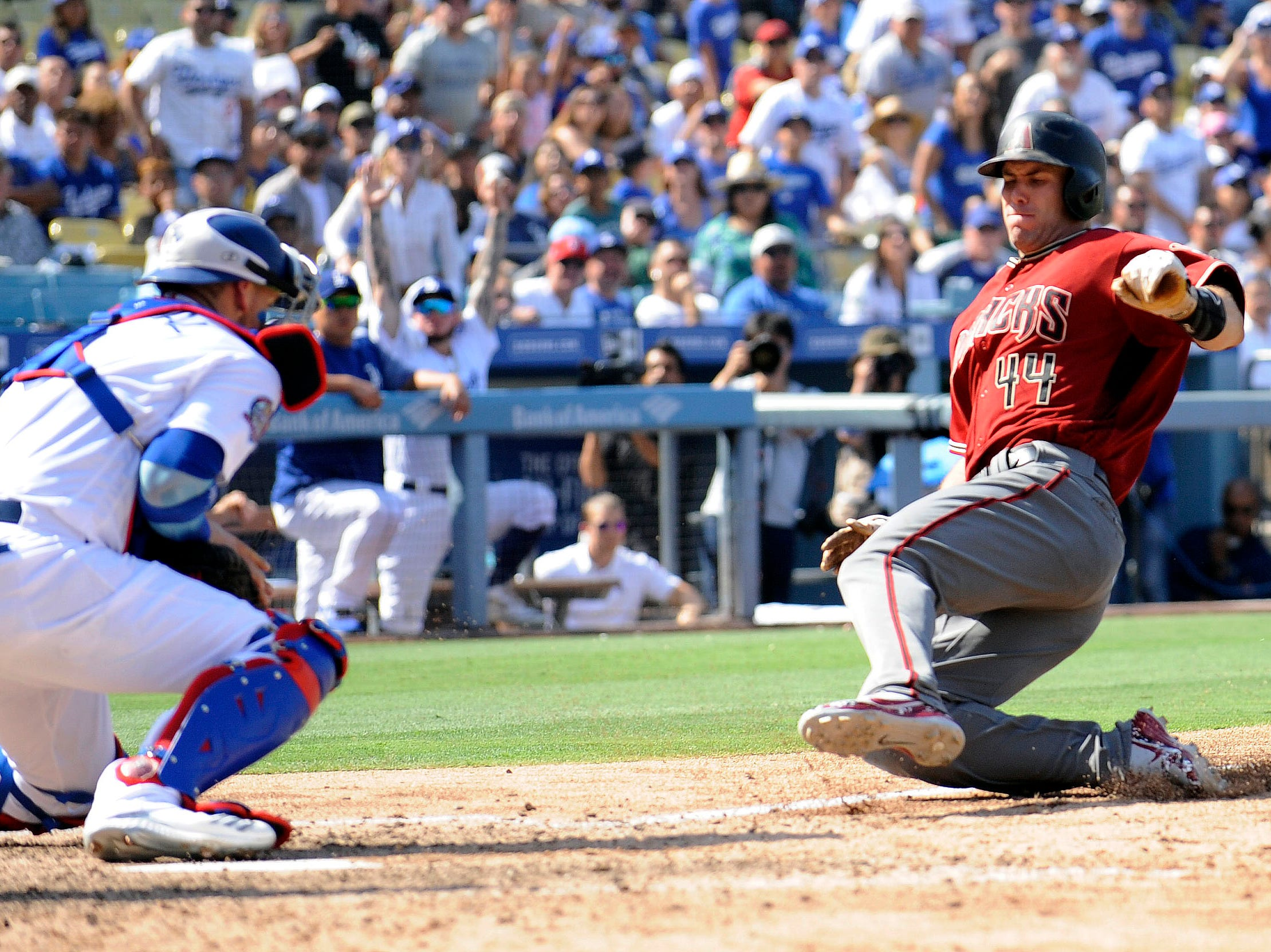 September 2, 2018; Los Angeles, CA, USA; Arizona Diamondbacks first baseman Paul Goldschmidt (44) reaches home but is tagged out by Los Angeles Dodgers catcher Yasmani Grandal (9) in the seventh inning at Dodger Stadium.  The call would be overturned on challenge.  Mandatory Credit: Gary A. Vasquez-USA TODAY Sports