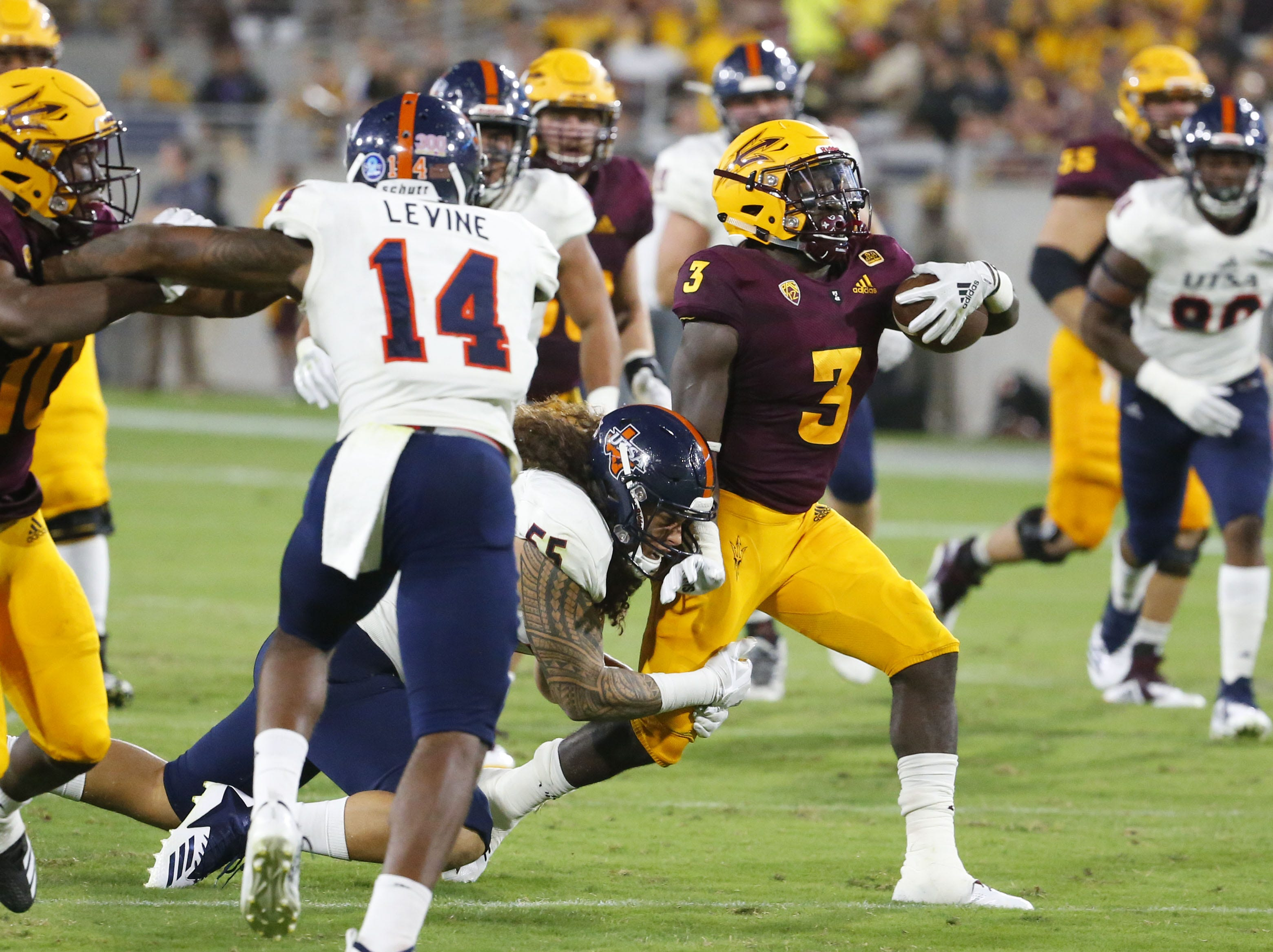 UTSA Roadrunners linebacker Josiah Tauaefa (55) attempts to tackle Arizona State Sun Devils running back Eno Benjamin (3) during a football game at Sun Devil Stadium in Tempe on September 1, 2018.