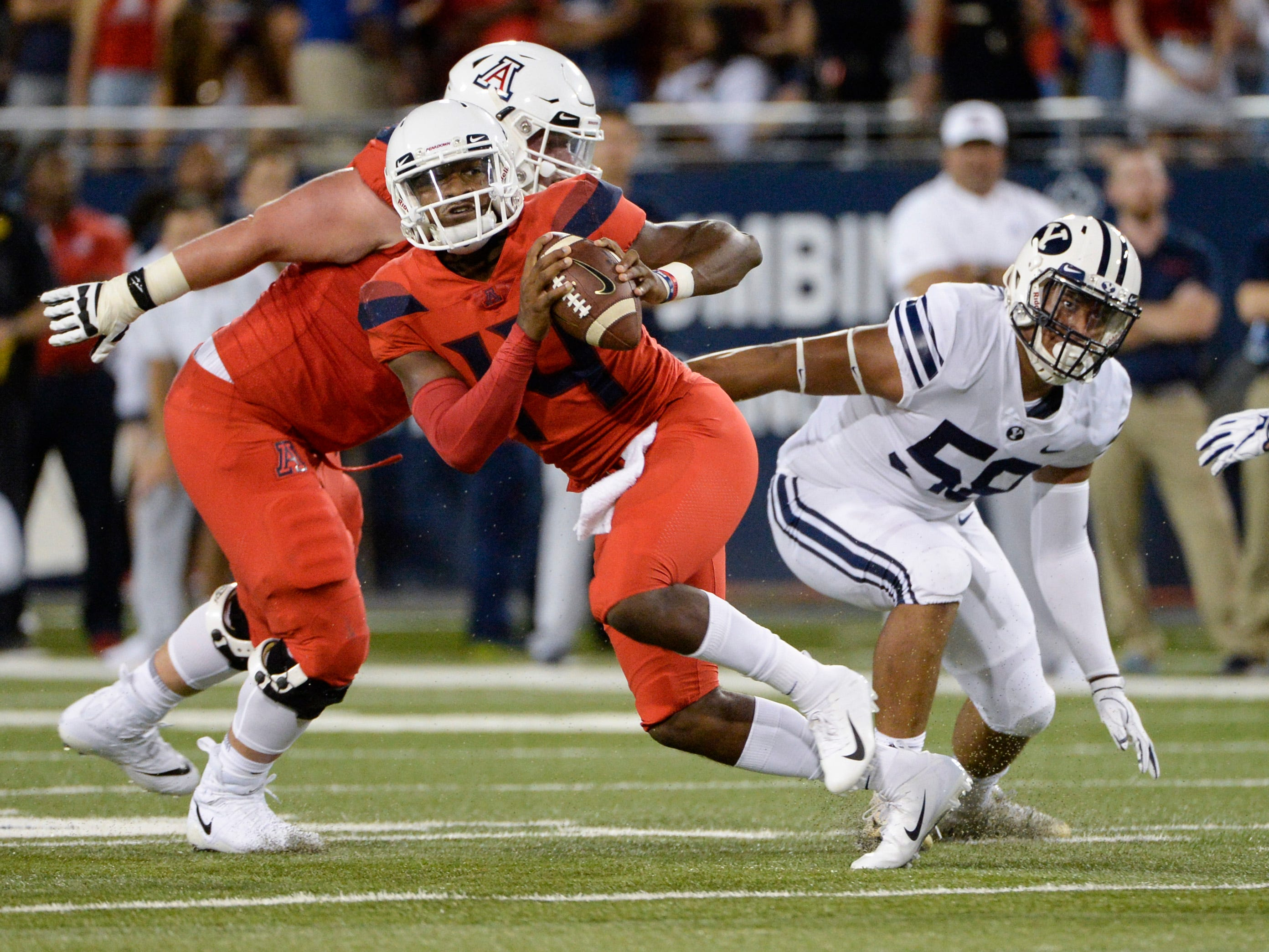 Sep 1, 2018; Tucson, AZ, USA; Arizona Wildcats quarterback Khalil Tate (14) looks to pass under pressure from Brigham Young Cougars defensive lineman Uriah Leiataua (58) during the first quarter at Arizona Stadium.