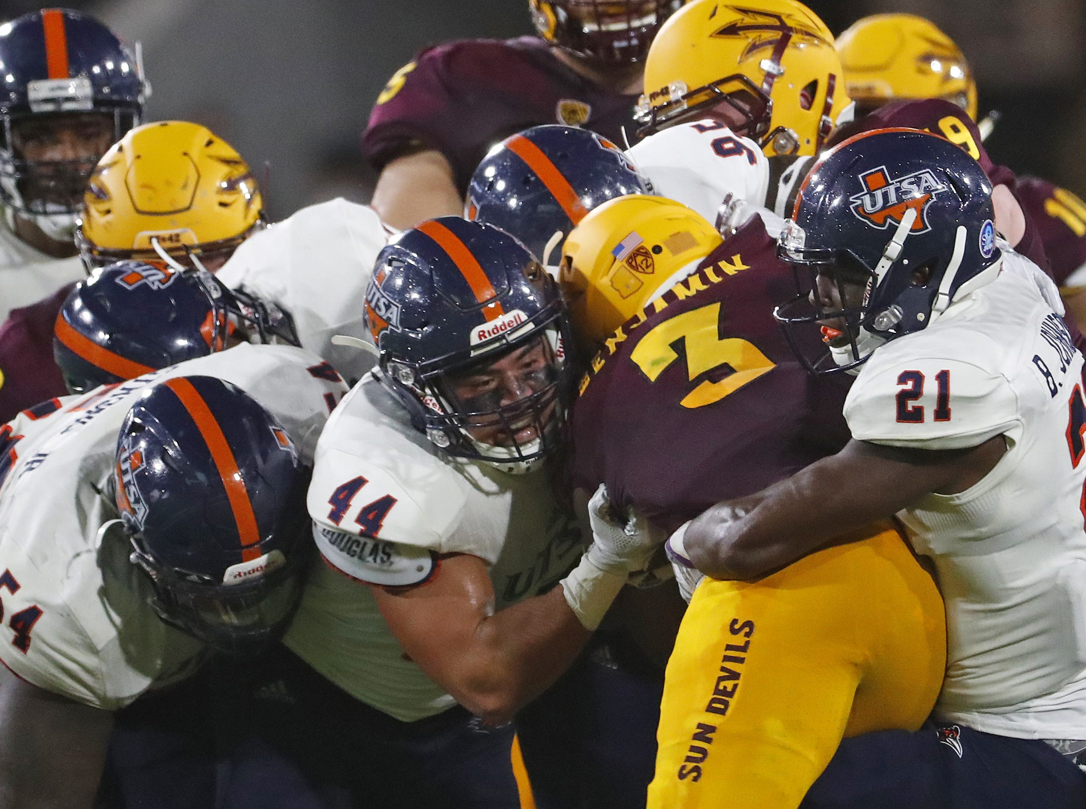UTSA Roadrunners linebacker Les Maruo (44) and safety Brenndan Johnson (21) tackle Arizona State Sun Devils running back Eno Benjamin (3) during the first half at Sun Devil Stadium in Tempe, Ariz. on Sept. 1, 2018.