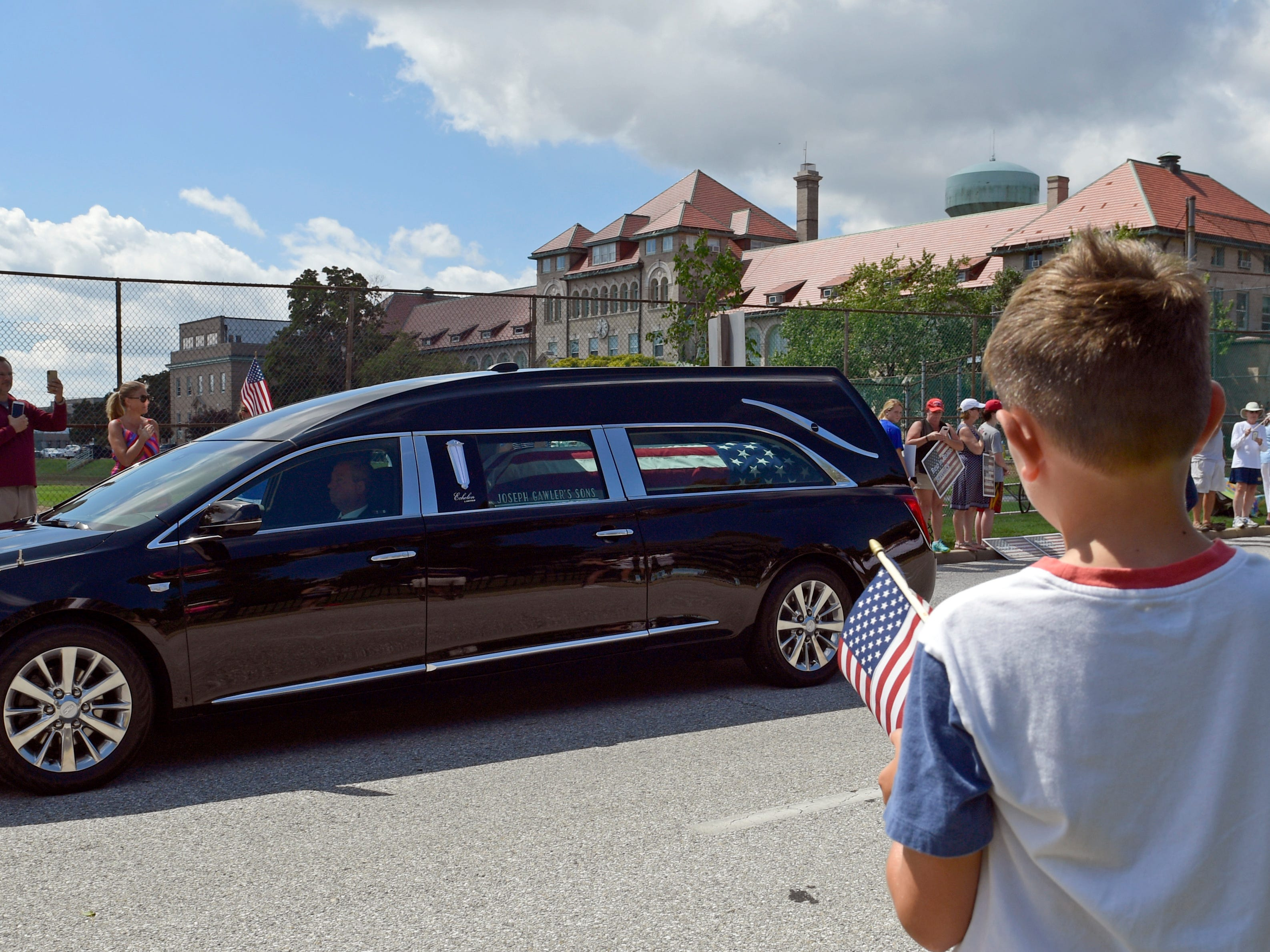 People watch as the funeral procession for Sen. John McCain arrives at the United States Naval Academy in Annapolis, Maryland, Sept. 2, 2018, for his funeral service and burial. McCain died Aug. 25 from brain cancer at age 81.