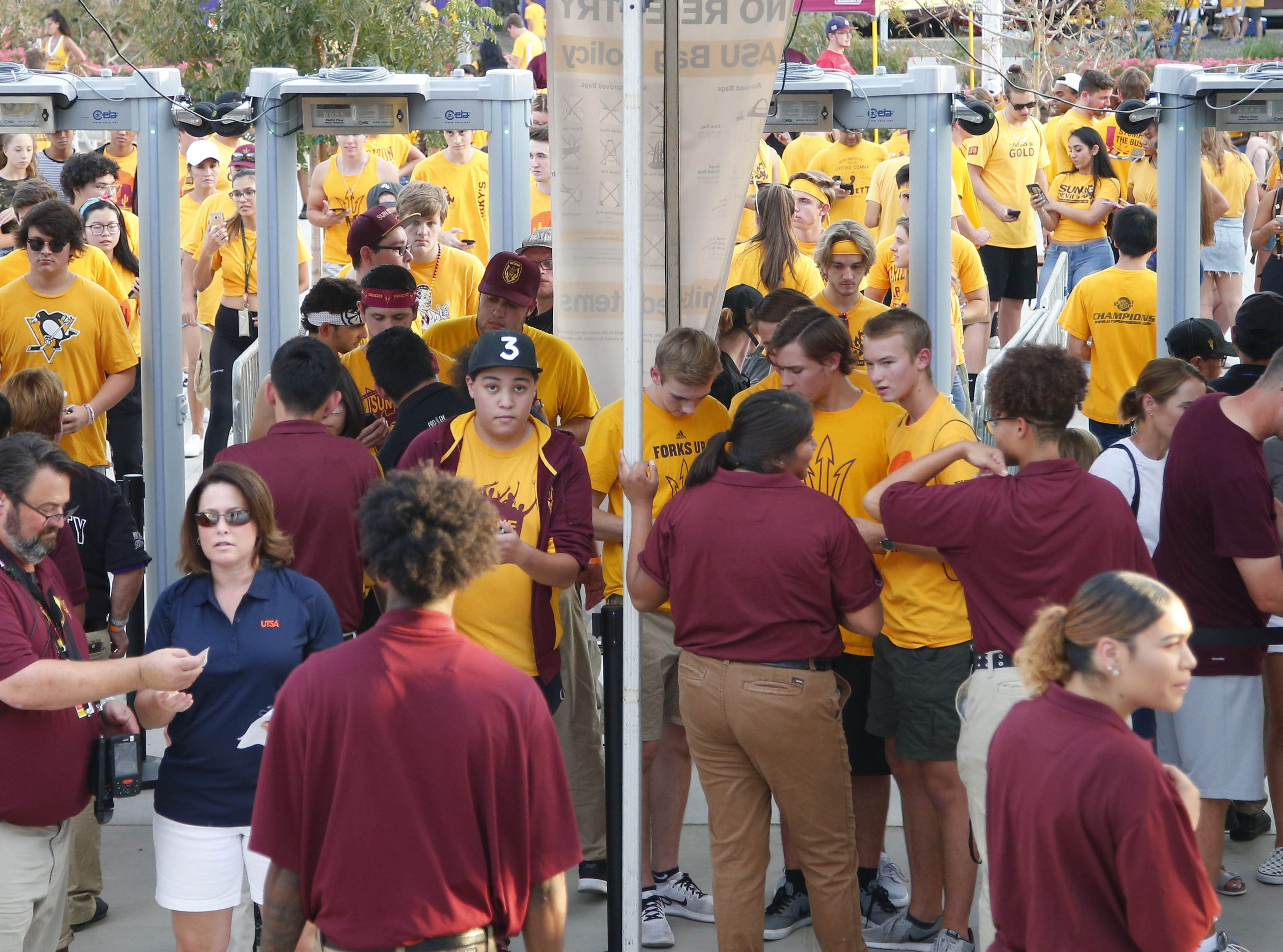 Fans file through mental detectors before the ASU vs. UTSA football game at Sun Devil Stadium in Tempe on September 1, 2018.