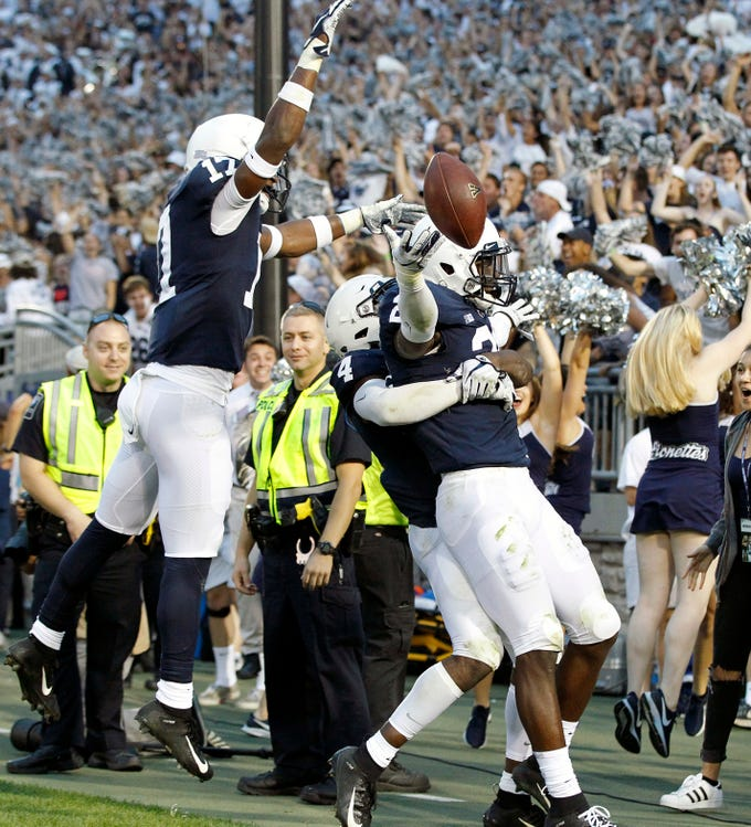 Penn State players mob teammate Amani Oruwariye (21) after he intercepted the ball in the end zone against Appalachian State in overtime of an NCAA college football game in State College, Pa., Saturday, Sept. 1, 2018. Penn State won 45-38 in OT. (AP Photo/Chris Knight)
