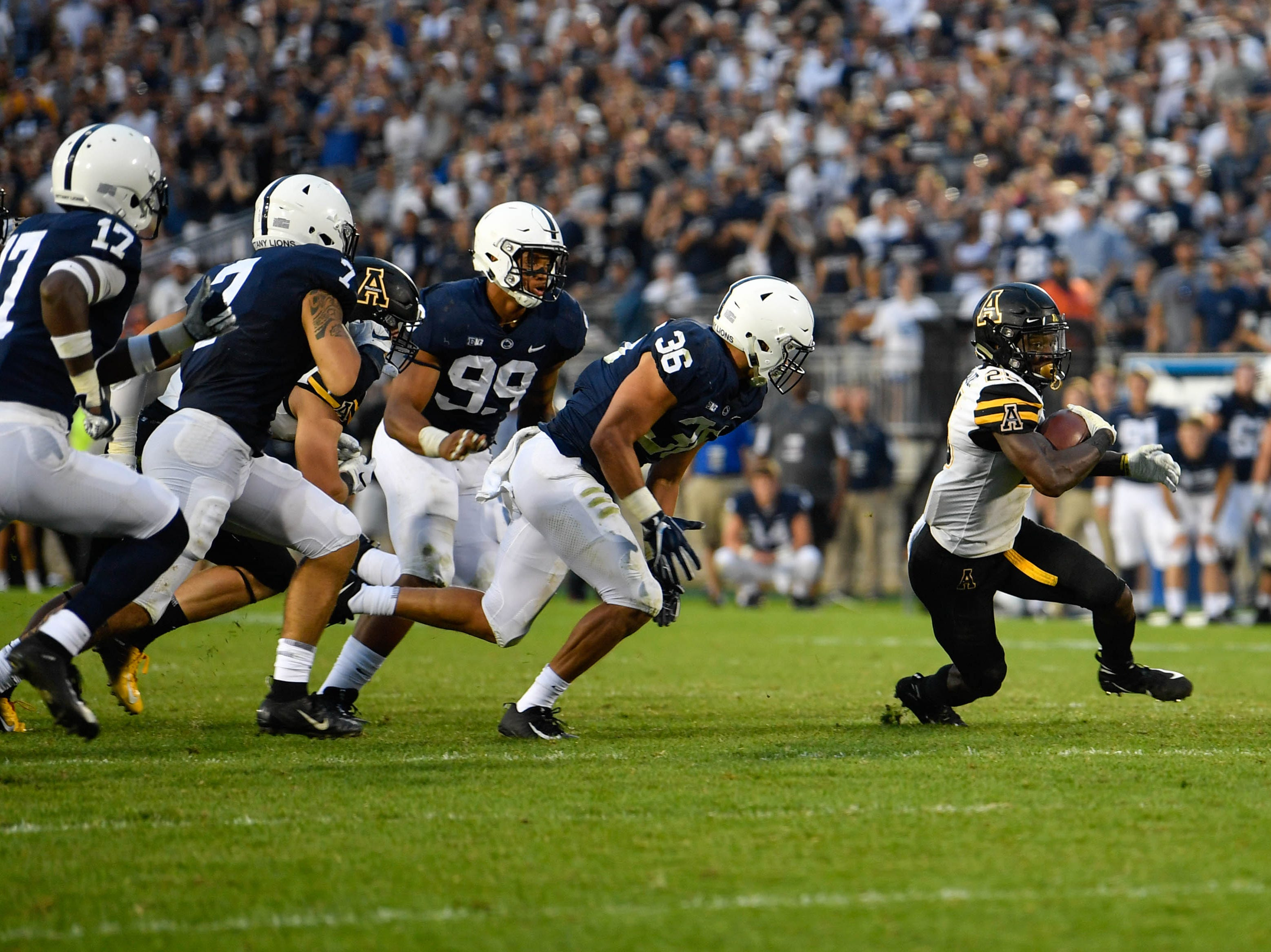 Penn State closes in on Jalin Moore as he tries to evade tackle in Beaver Stadium.