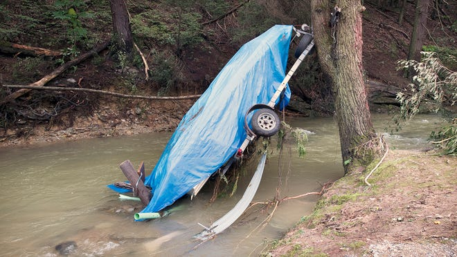 A boat on a trailer is suspended from a tree, after it was washed downstream during heavy rain Aug. 31, 2018 along Kline Road in Chanceford Township. The trailer tongue was caught in the tree and the current bent the steel frame pulling the boat and trailer around the tree.