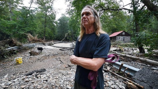 David McSwain stands in the middle what was Kline Road on Sunday where it intersects Otter Creek in Chanceford Township. McSwain, who lives nearby, came to check on a friend who had his house washed away.