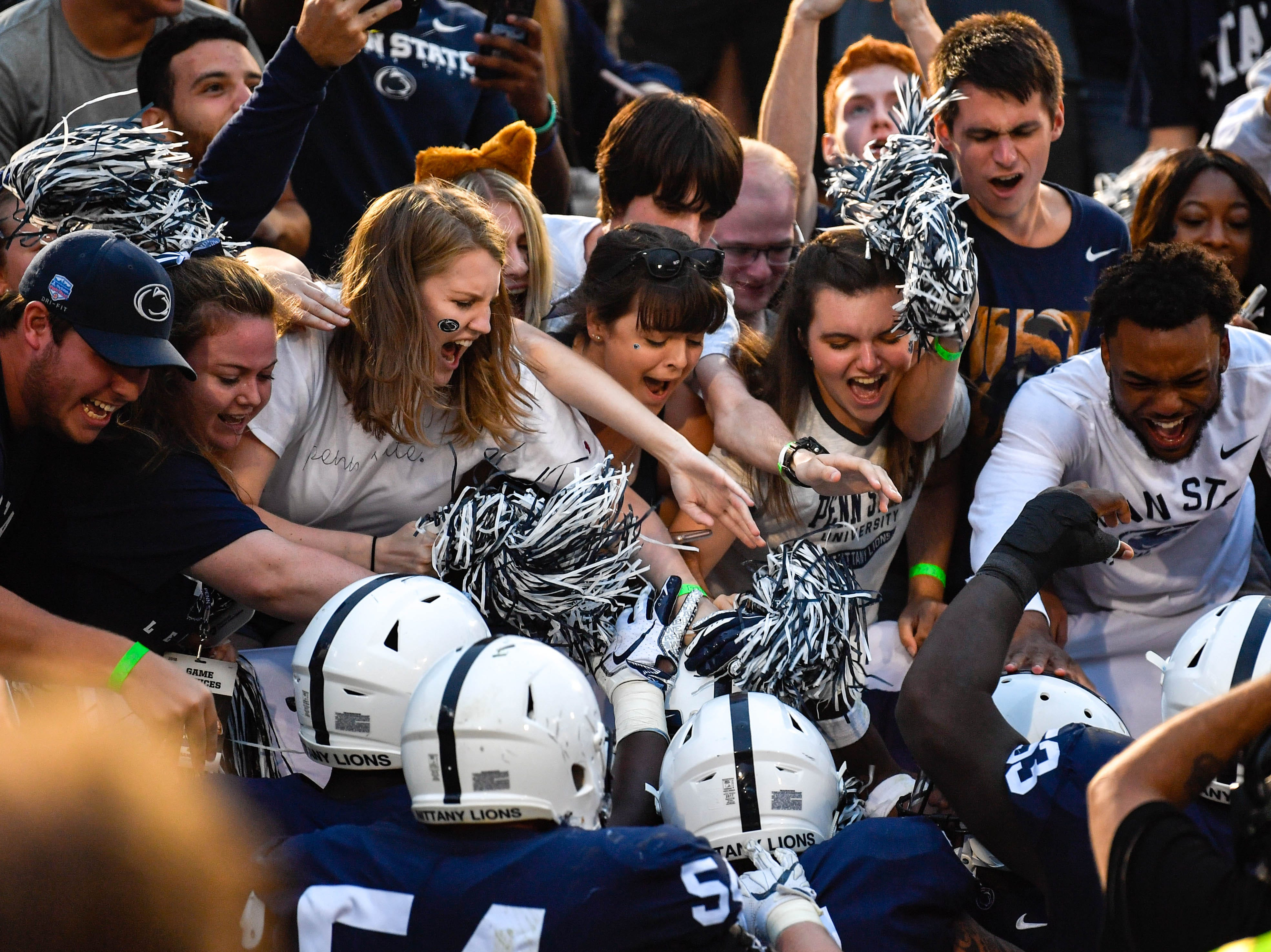 Penn State players celebrate the overtime win with their fans after defeating Appalachian State in a nail biter.