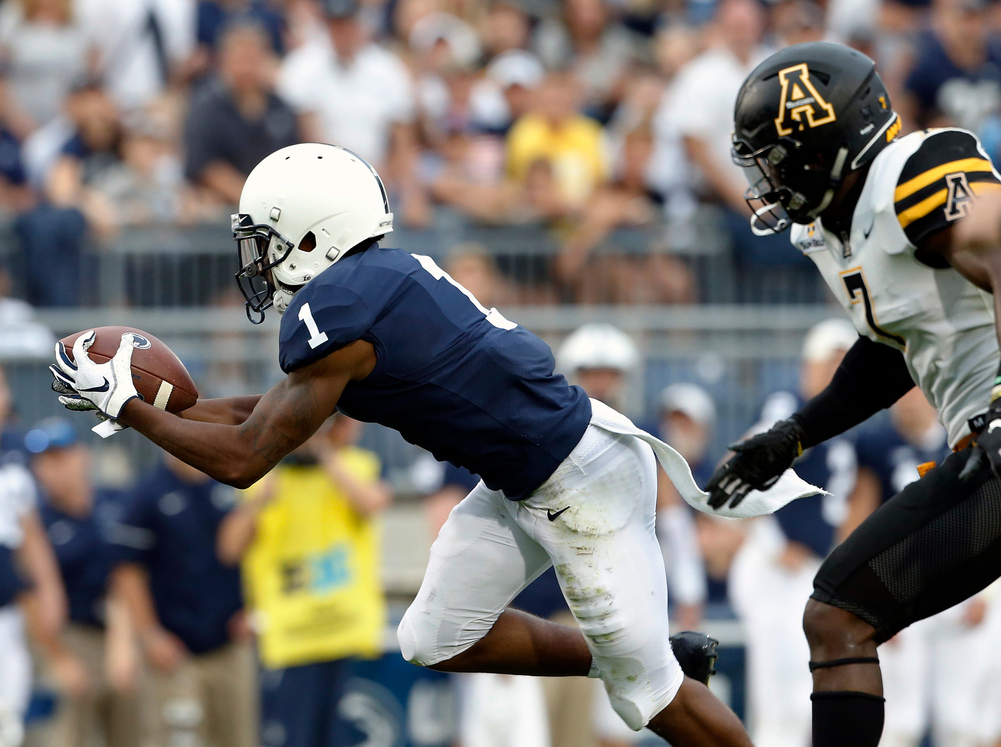 Penn State's KJ Hamler (1) makes a catch in front of Appalachian State's Josh Thomas (7) during the second half of an NCAA college football game in State College, Pa., Saturday, Sept. 1, 2018. Penn State won 45-38 in overtime. (AP Photo/Chris Knight)