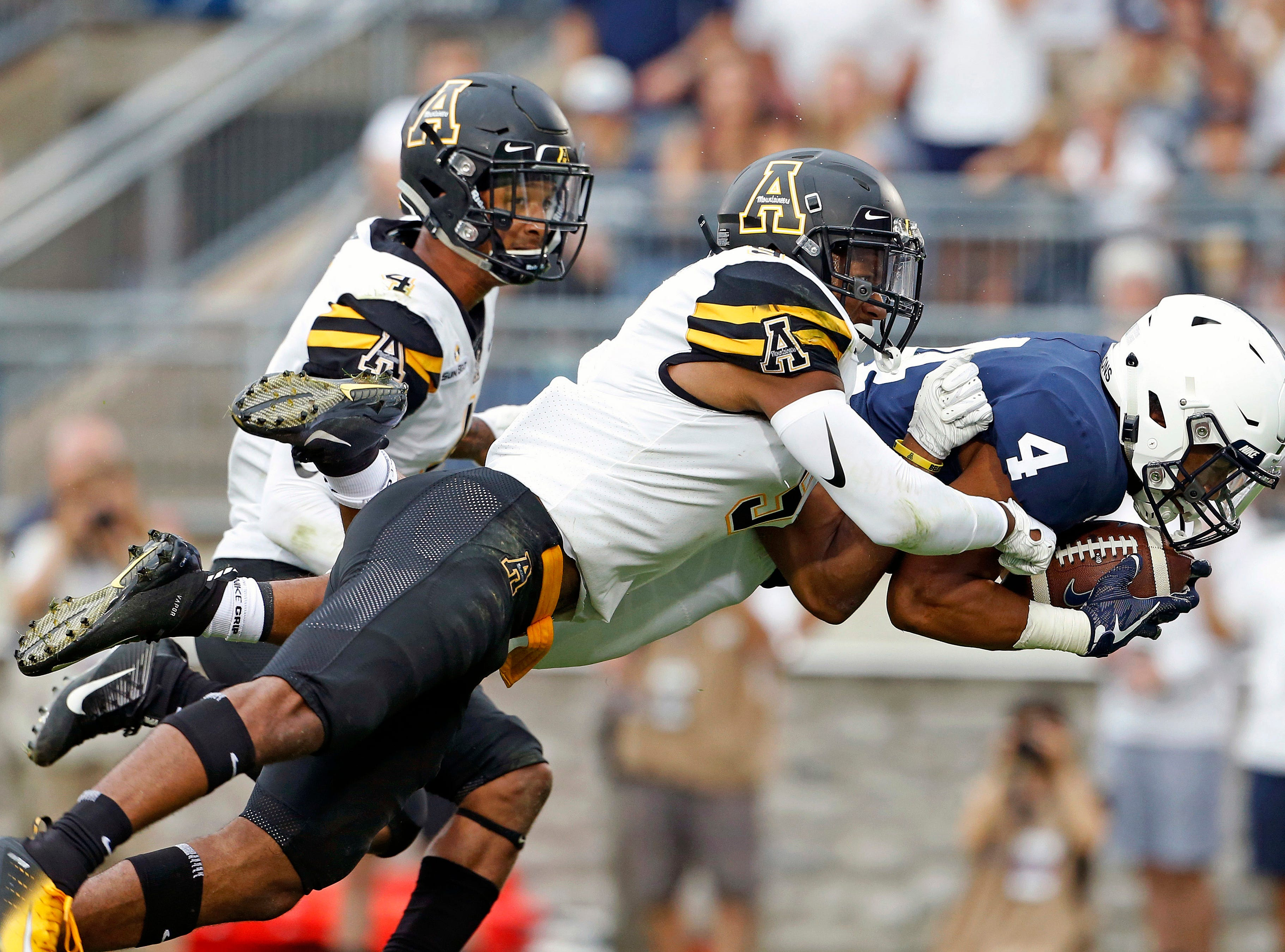 Penn State's Ricky Slade (4) dives in for a touchdown as Appalachian State's Austin Exford (9) and Clifton Duck (4) try and to make the tackle during the second half of an NCAA college football game in State College, Pa., Saturday, Sept. 1, 2018. Penn State won 45-38 in overtime. (AP Photo/Chris Knight)