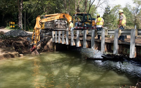PennDOT works on stabilizing a bridge abutment Sunday on Lucky Road where is crosses Otter Creek that was damaged during heavy rain Friday. More than 100 PennDOT workers were working on flood damaged roads over the holiday weekend. Bridges won't reopen until they are inspected.