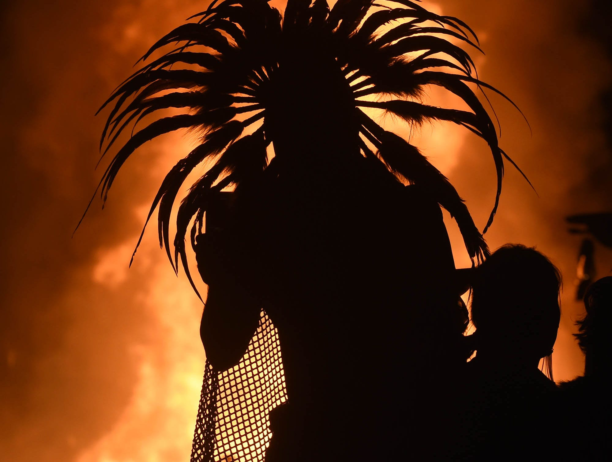 A person in costume watches the man burns on the playa on Sept. 1, 2018
