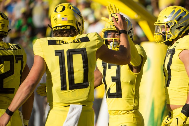 Sep 1, 2018; Eugene, OR, USA; Oregon Ducks wide receiver Dillon Mitchell (13) celebrates with quarterback Justin Herbert (10) after catching a touchdown pass during the first half against the Bowling Green Falcons at Autzen Stadium. Mandatory Credit: Troy Wayrynen-USA TODAY Sports