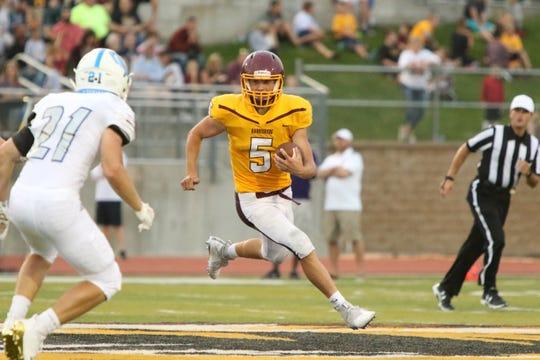 Jack Teigen of Harrisburg looks to sprint around the defensive effort of C.J. Stukel of O'Gorman during Saturday's game in Harrisburg.