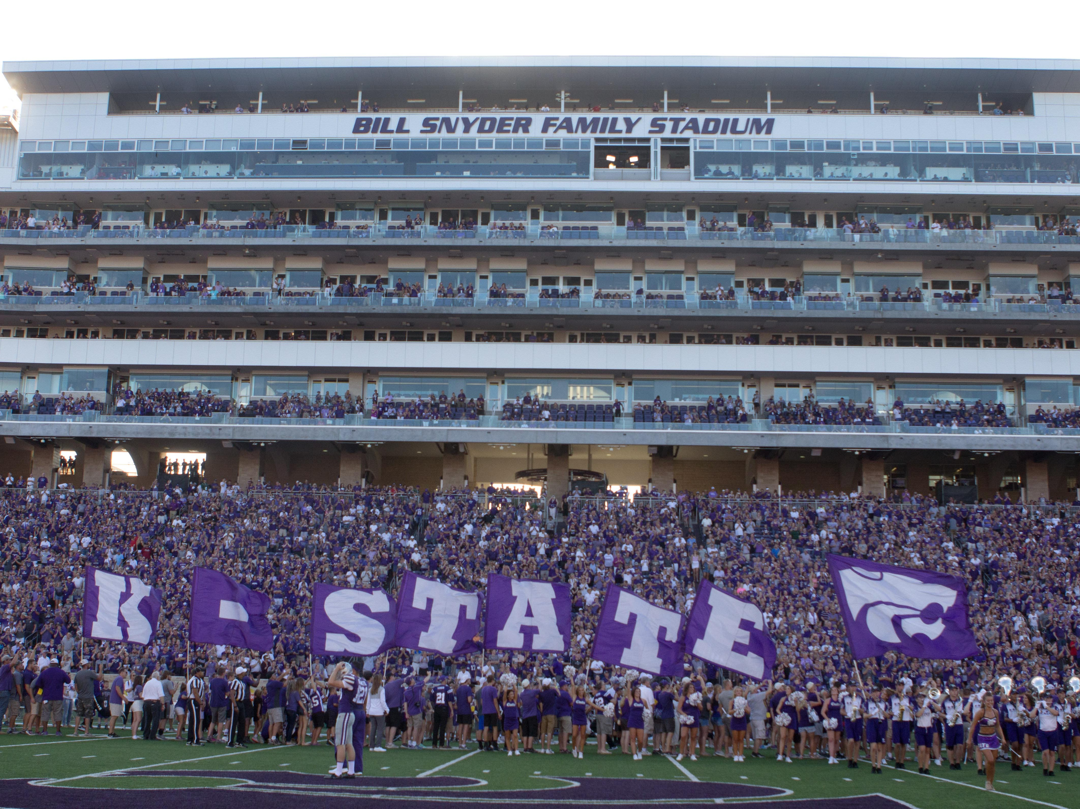 Sep 1, 2018; Manhattan, KS, USA; Kansas State Wildcats cheerleaders carry flags onto the field before a game between the Wildcats and the South Dakota Coyotes at Bill Snyder Family Stadium. Mandatory Credit: Scott Sewell-USA TODAY Sports