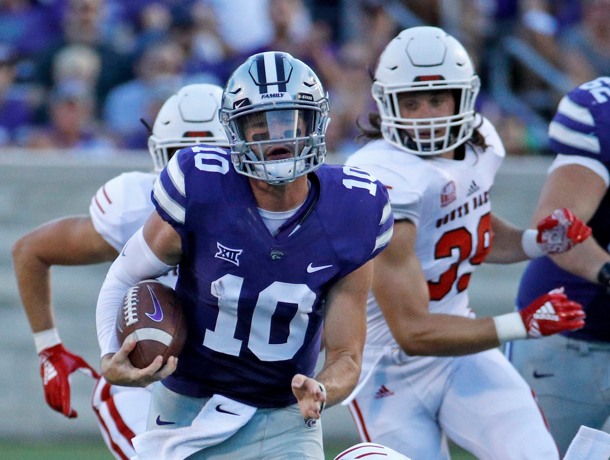 Kansas State quarterback Skylar Thompson (10) gets past South Dakota defensive back Elijah Reed (4) as he runs for a first down during the first half of an NCAA college football game Saturday, Sept. 1, 2018, in Manhattan, Kan. (AP Photo/Charlie Riedel)