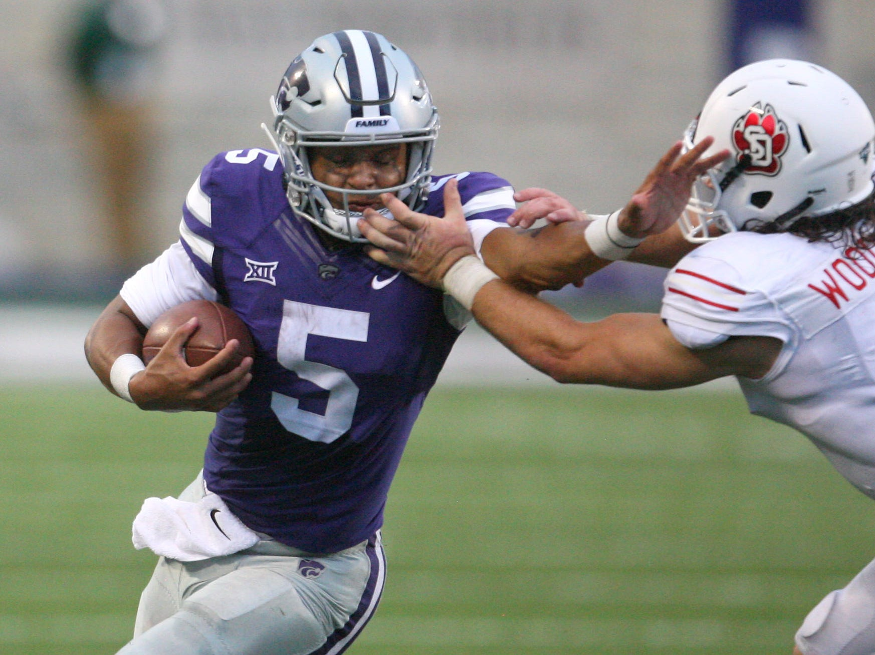Sep 1, 2018; Manhattan, KS, USA; Kansas State Wildcats quarterback Alex Delton (5) tries to stiff arm South Dakota Coyotes linebacker Brian Woodward (5) during second quarter at Bill Snyder Family Stadium. Mandatory Credit: Scott Sewell-USA TODAY Sports