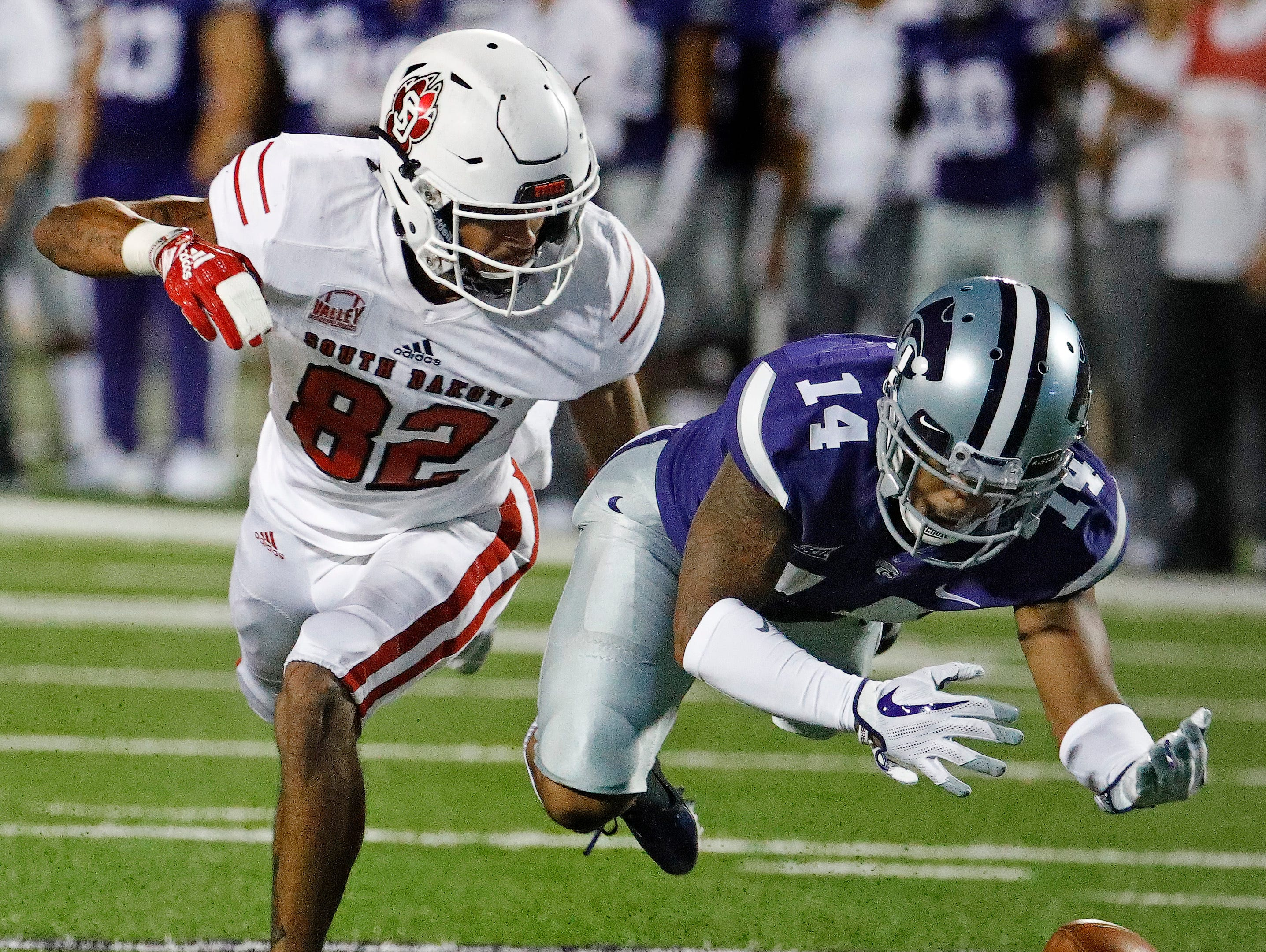 Kansas State defensive back Kevion McGee (14) breaks up a pass intended for South Dakota wide receiver Dakarai Allen (82) during the second half of an NCAA college football game Saturday, Sept. 1, 2018, in Manhattan, Kan. Kansas State won 27-24. (AP Photo/Charlie Riedel)