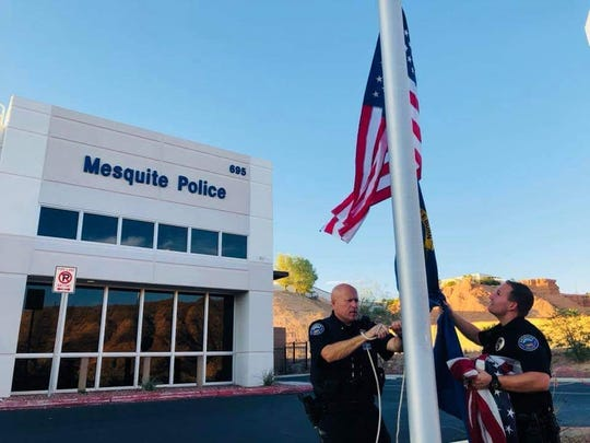 Patrol Lt. Rob Stepp and Officer Skyler Vent replace the American flag at the police department with a new one on Flag Day, June 14, 2018.