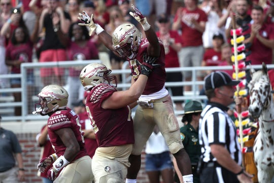 FSU's Cole Minshew celebrates with Cam Akers after his 63-yard TD run against Syracuse during their game at Doak Campbell Stadium last season.