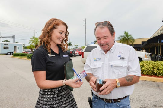 St. Lucie Battery & Tire Brand Manager Lindsey Concannon, left, sells a raffle ticket for the Diamond Lil' Tiny Home to Ed Roseberry from City of Fort Pierce at the Treasure Coast Builders Association's Fun After Five networking event.