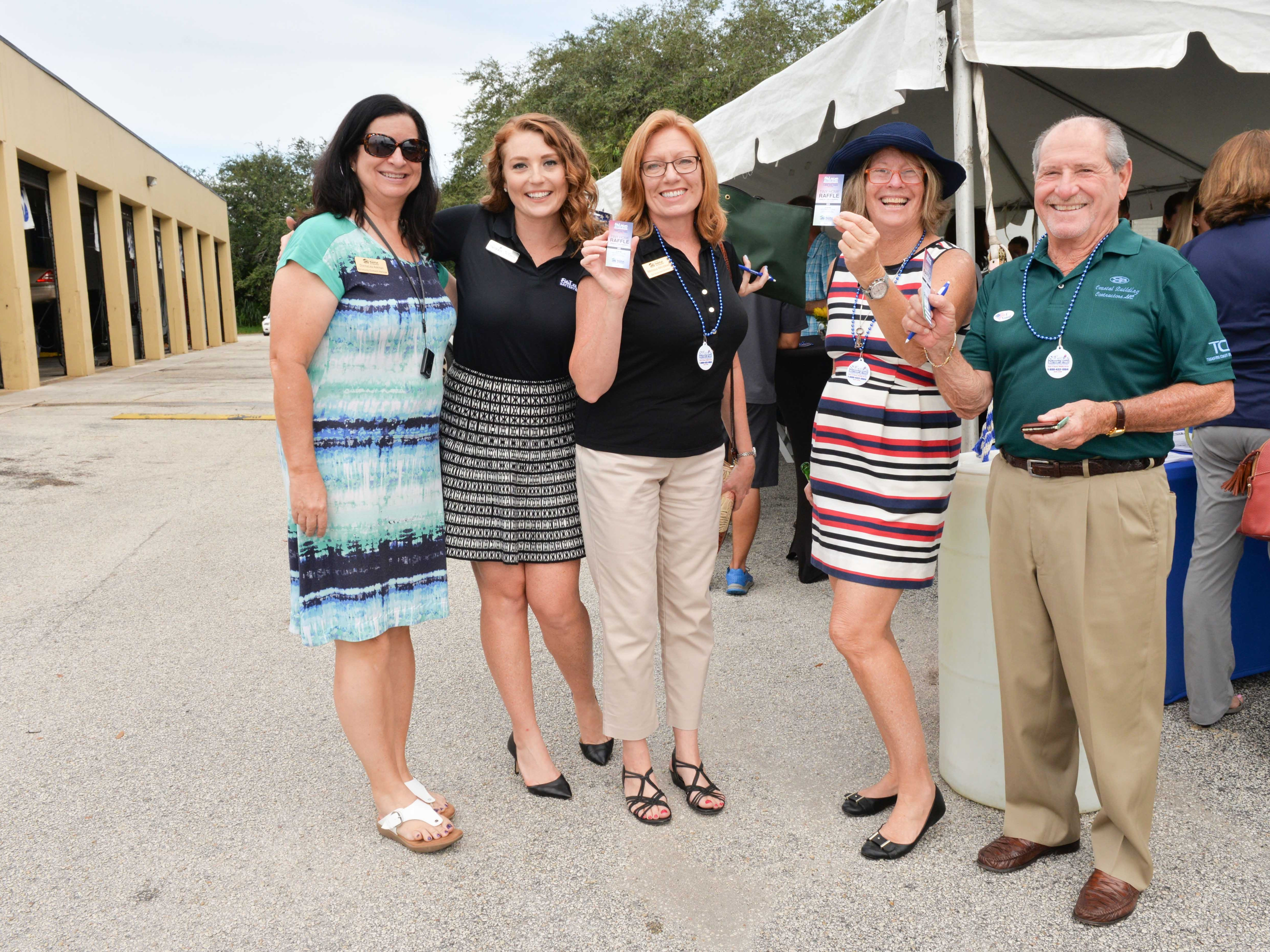 DonnaLea Askman, left, Lindsey Concannon, Melissa Winstead, Patti Hancock and Jeff Braun with their $20 raffle tickets for the 188-square-foot Diamond Lil' Tiny Home.