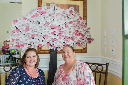 Charlotte LaChance and Tracy Jahn pose in front of the Hearts of Hope tree on display at the Hearts of Hope Bingo benefit at  Gator Trace Golf and Country Club in Fort Pierce.