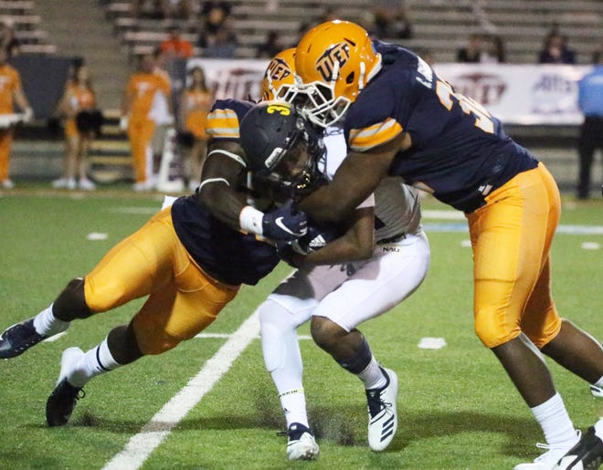 Northern Arizona running  back Aramis Aldredge, 31, is sandwiched by UTEP defenders near the end of the game with UTEP Saturday night. The Lumberjacks beat UTEP in the Miner's home opener 30-10.