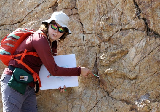 Tour guide Georgina Rodriguez-Gonzalez pointed to traces of dinosaur tracks on a hike.