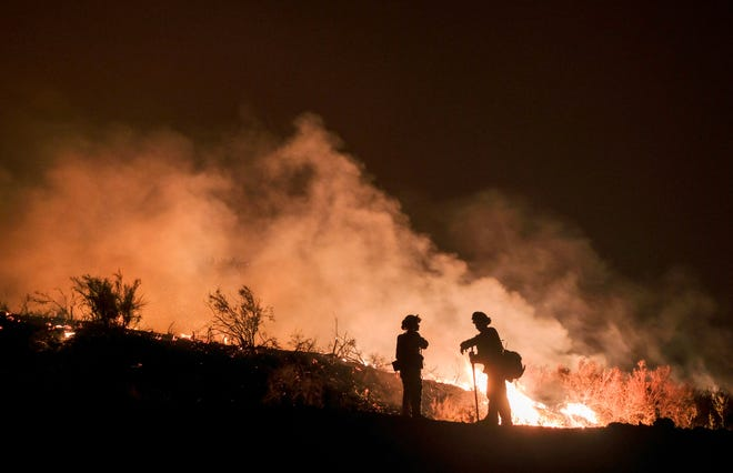 In this Aug. 9 photo, firefighters keep watch the Holy Fire burning in the Cleveland National Forest in Lake Elsinore. Researchers have expanded a health-monitoring study of wildland firefighters after a previous study found season-long health declines and deteriorating reaction times.
